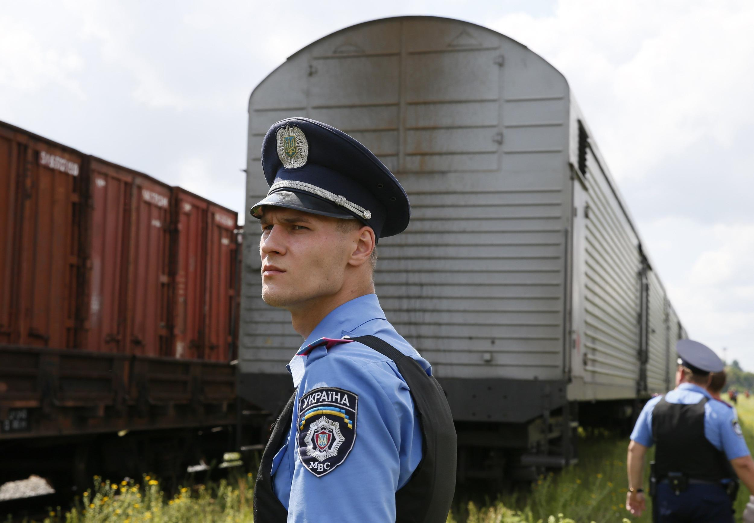 Image: A Ukrainian policeman watches as a train carrying the remains of Malaysia Airlines MH17 victims arrives in Kharkiv