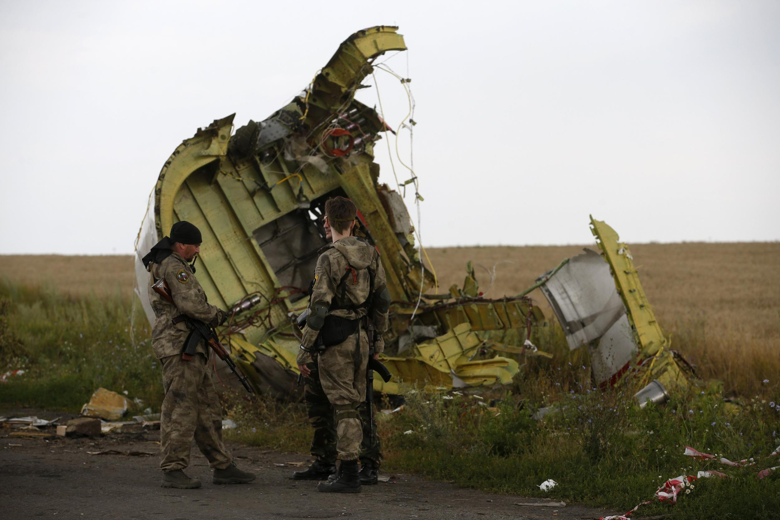 Armed pro-Russian separatists stand guard as monitors from the Organization for Security and Cooperation in Europe (OSCE) inspect the crash site of Malaysia Airlines Flight MH17.