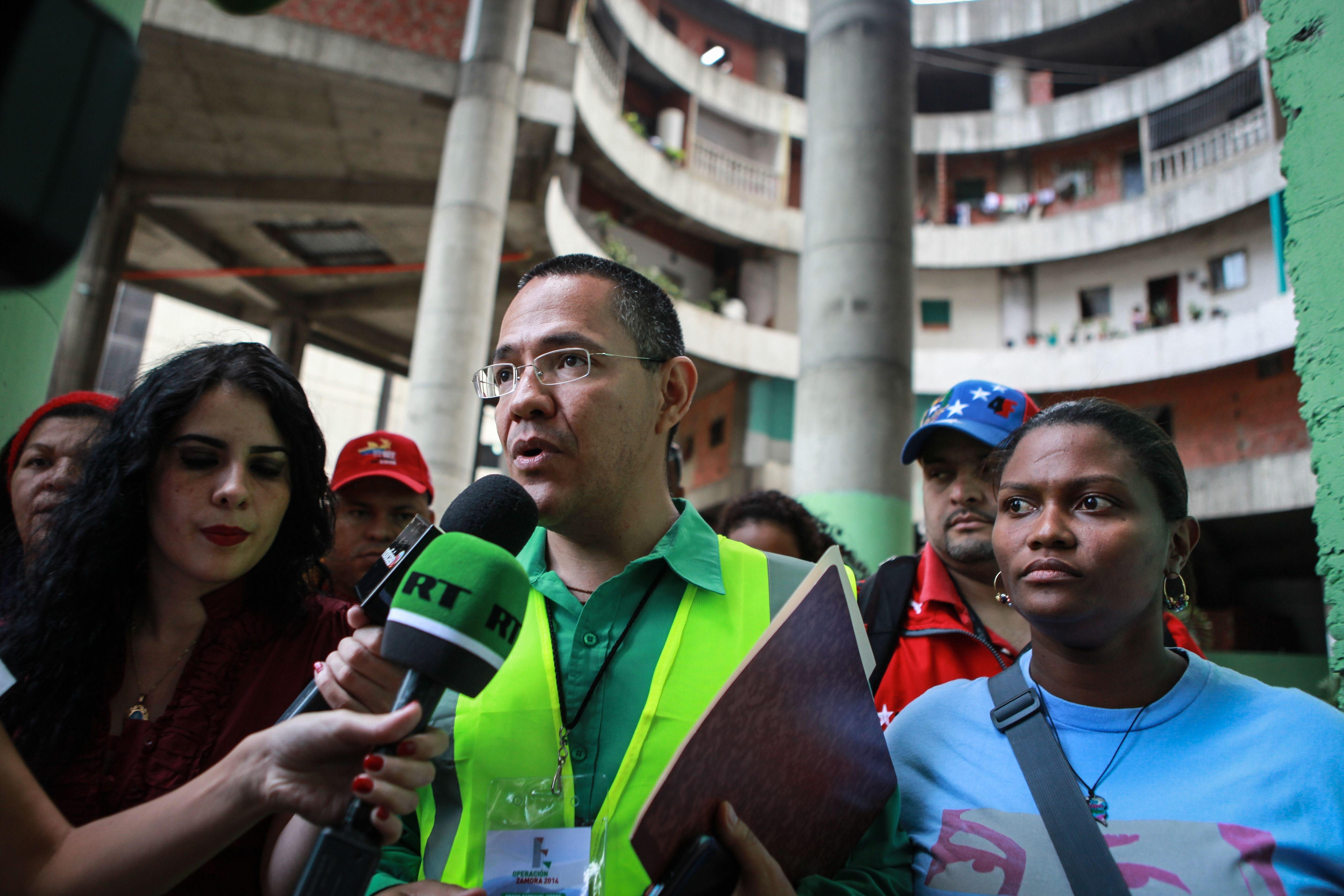 Image: The Minister of State for the Urban Transformation of Greater Caracas, Ernesto Villegas, speaks to the press during the eviction of the Tower of David