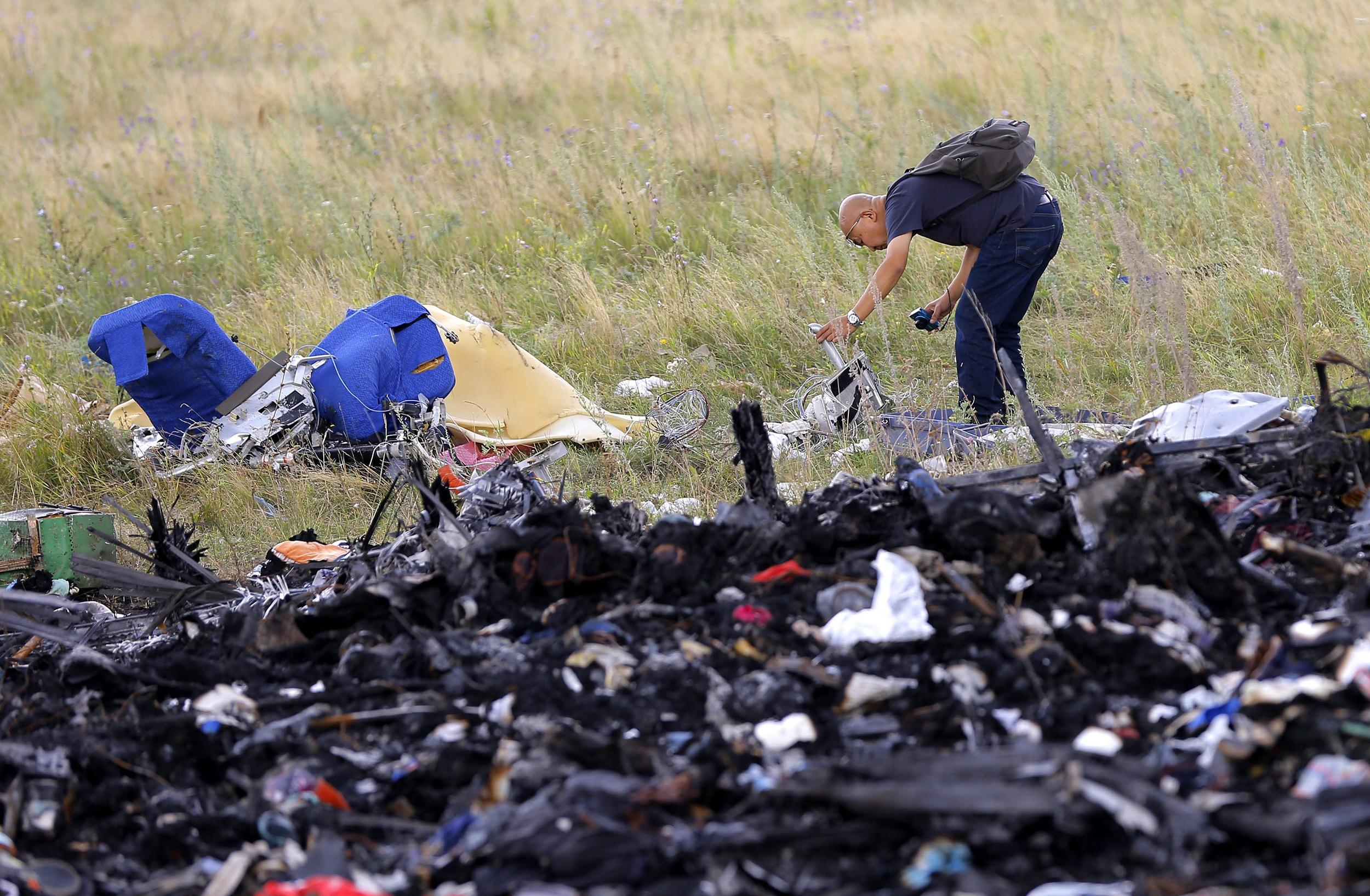 Image: A Malaysian expert checks debris at the main crash site of the Boeing 777 Malaysia Airlines flight MH17, which crashed flying over the eastern Ukraine region