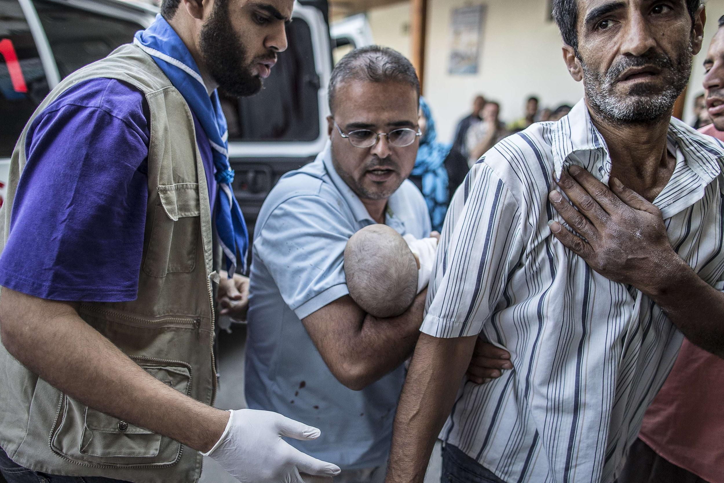 Image: Paramedics carry a six-month-old baby into hospital after Israeli strike