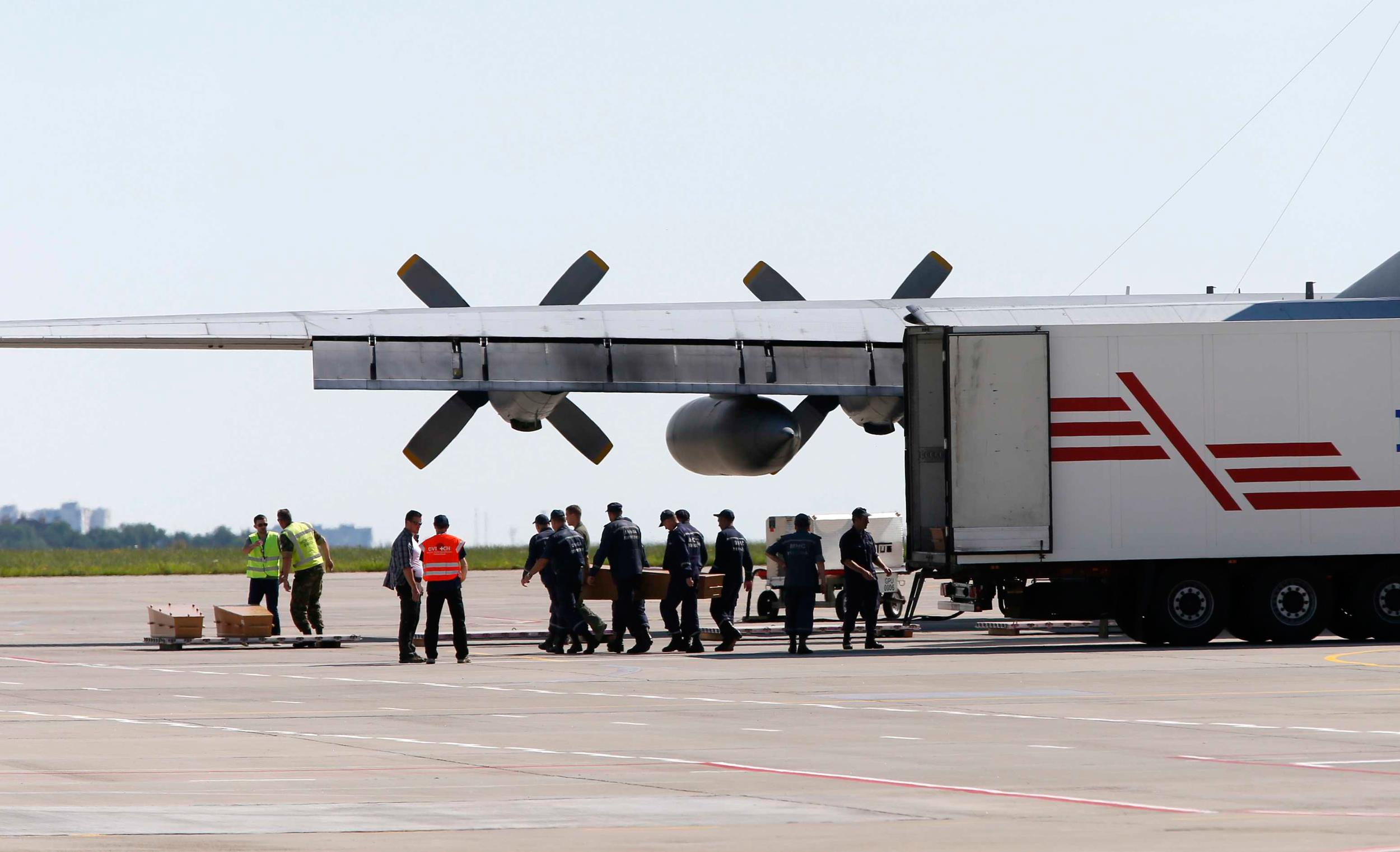 Image: People load coffins carrying some of remains of Malaysia Airlines MH17 victims to a transport plane at Kharkiv airport