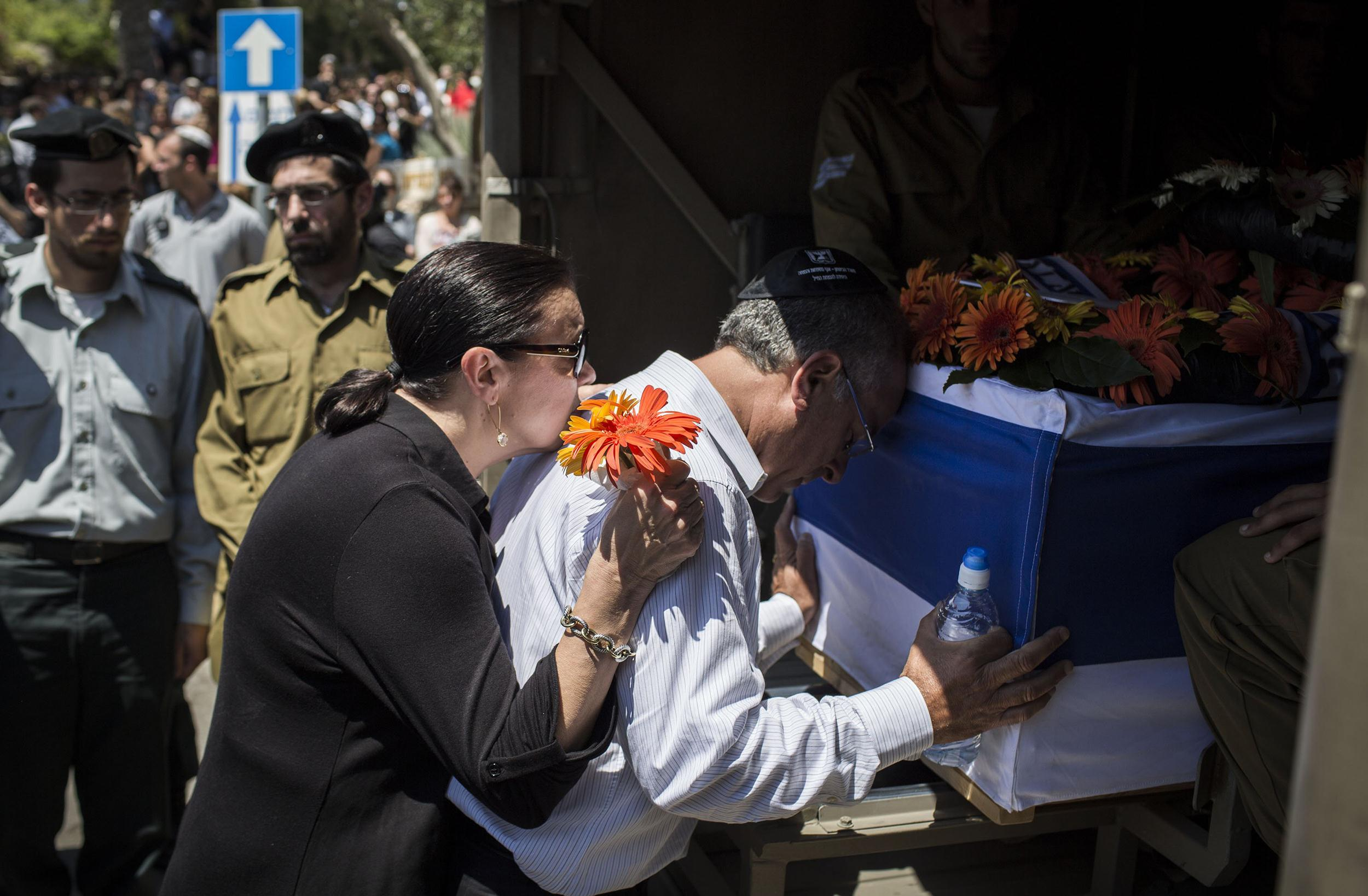 Image: The parents of Sergeant Max Steinberg grieve at his coffin