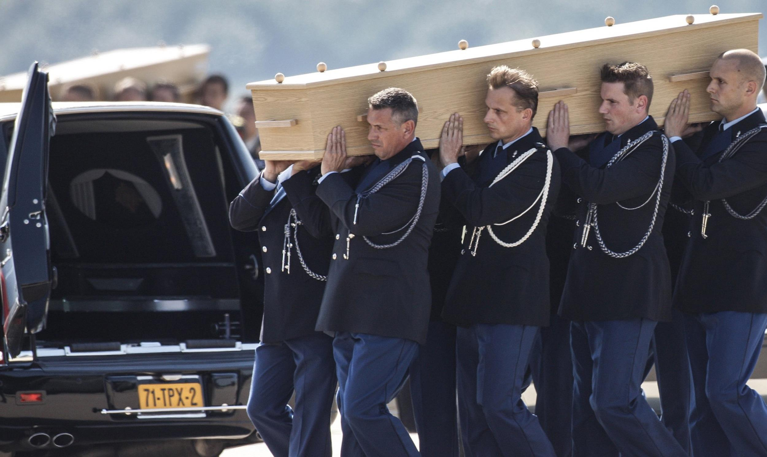 Image: Coffins of the victims of Malaysia Airlines MH17 downed over rebel-held territory in eastern Ukraine, are loaded into hearses on the tarmac during a national reception ceremony at Eindhoven airport