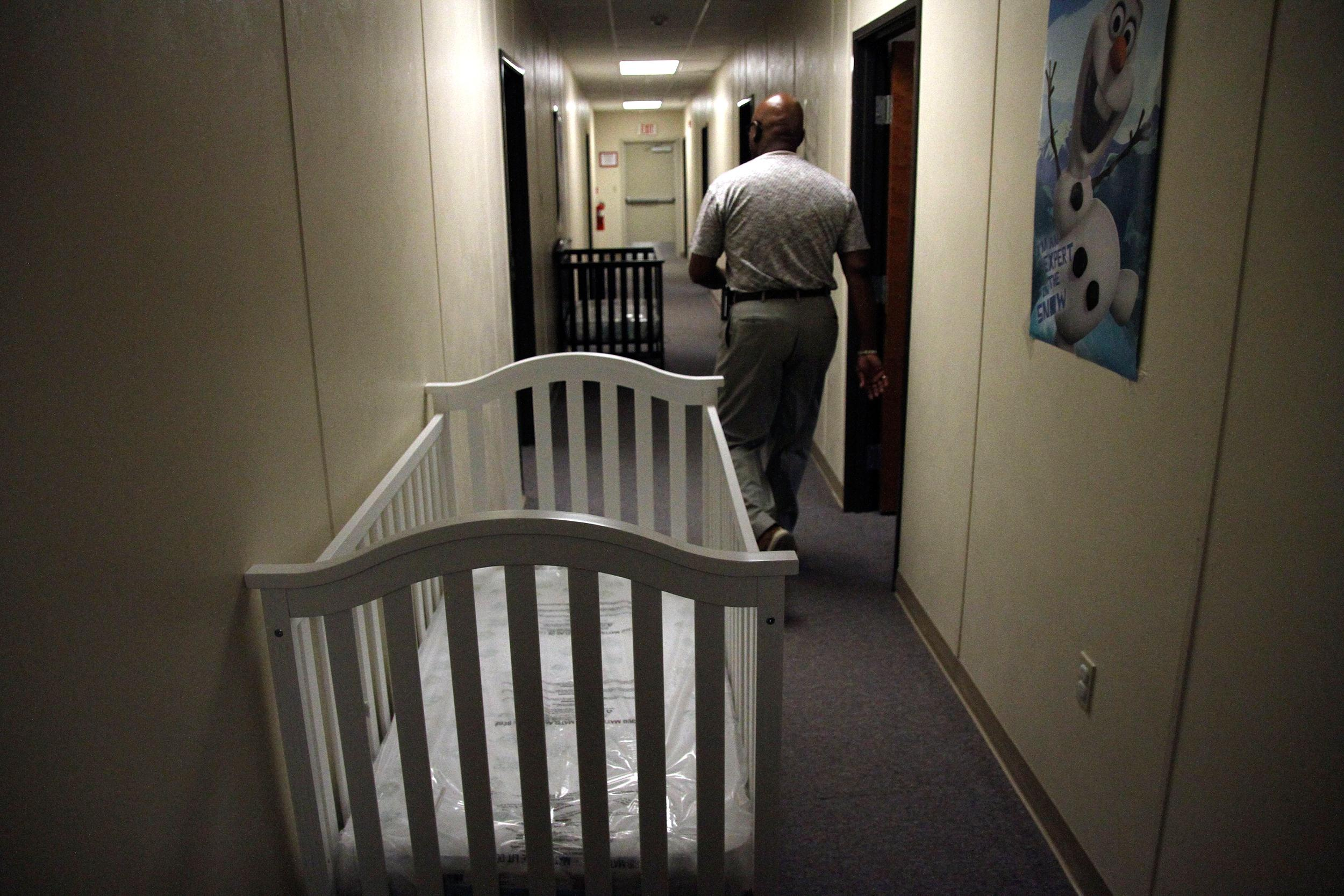 Image: A federal employee is seen walking past cribs inside of the barracks for law enforcement trainees turned into immigrant detention center at the Federal Law Enforcement Center (FLETC) in Artesia, N.M.