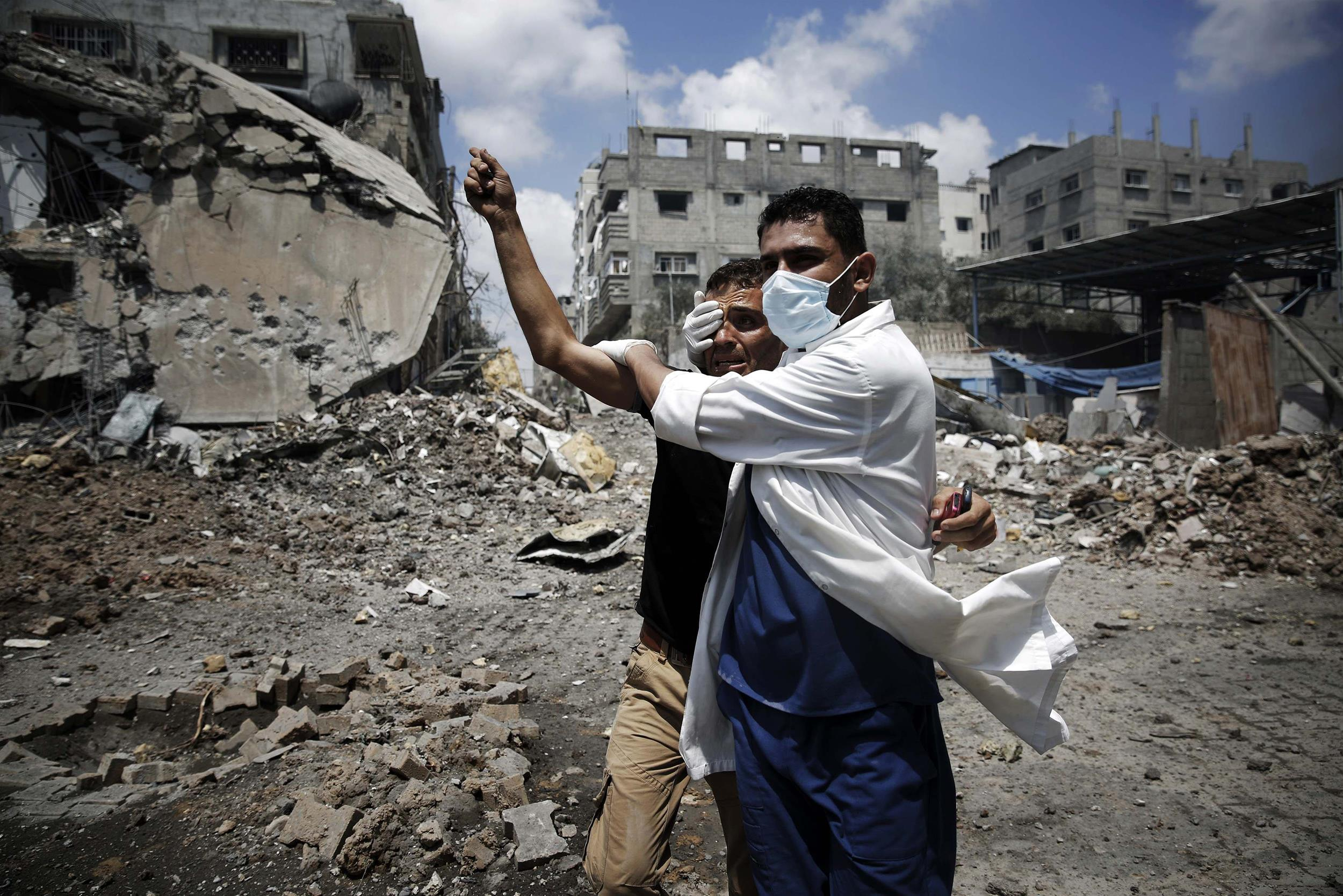 Image: A medic helps a Palestinian in the Shejaia neighbourhood, which was heavily shelled by Israel during fighting, in Gaza City