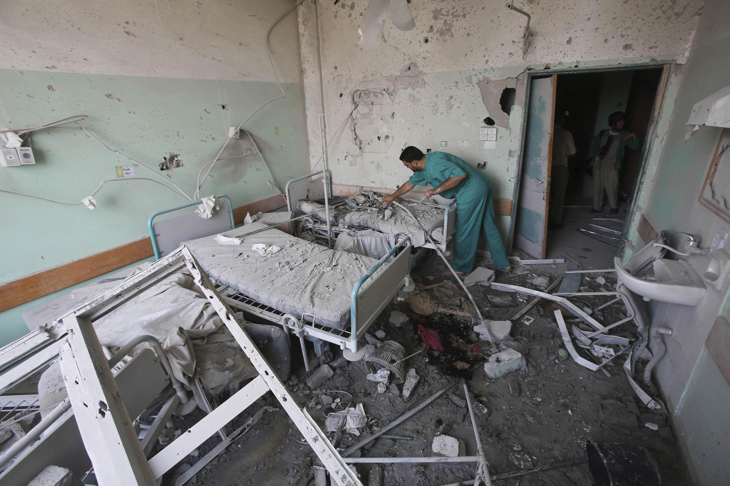 Image: Palestinian medic inspects a damaged room at Al-Aqsa hospital after it was shelled Monday