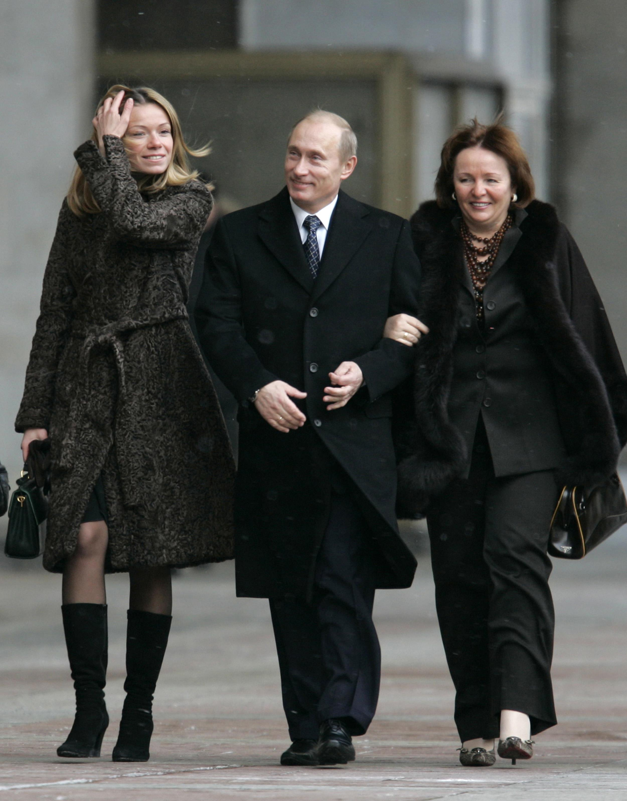Image: Russian President Vladimir Putin, daughter Maria, left, and his wife Lyudmila, right, walk to a polling station in Moscow, on Dec. 2, 2007.