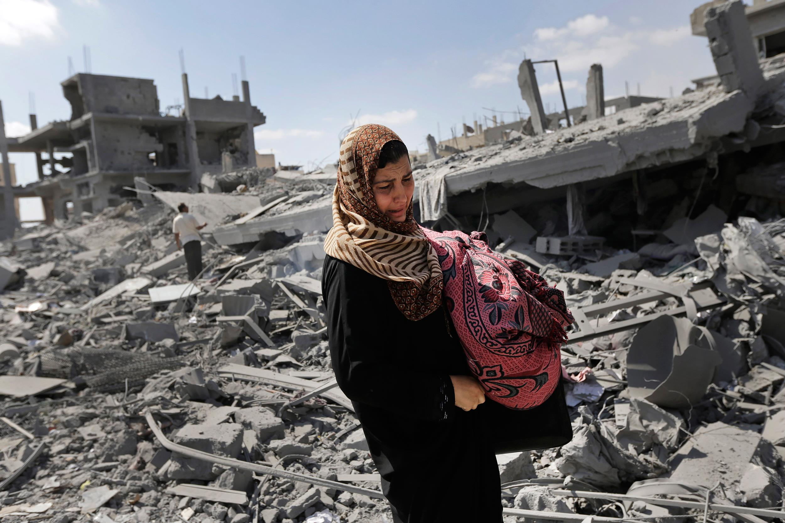 Image: A Palestinian woman carries her belongings past the rubble of houses destroyed by Israeli strikes in Beit Hanoun, northern Gaza Strip