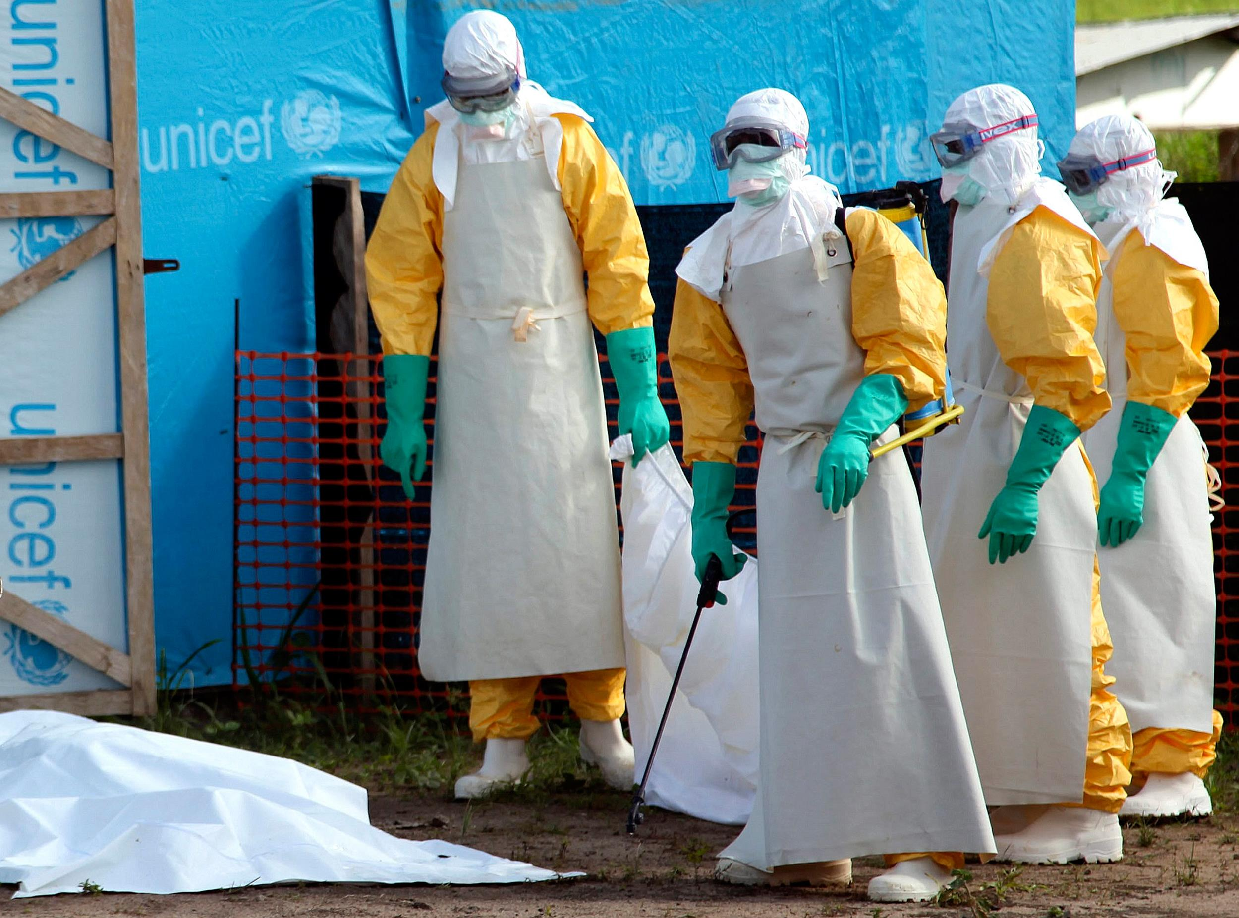 Image: Liberian health workers about to load the body of a woman who died from the Ebola virus into a pickup at the isolation unit in Foya, Lofa County, Liberia