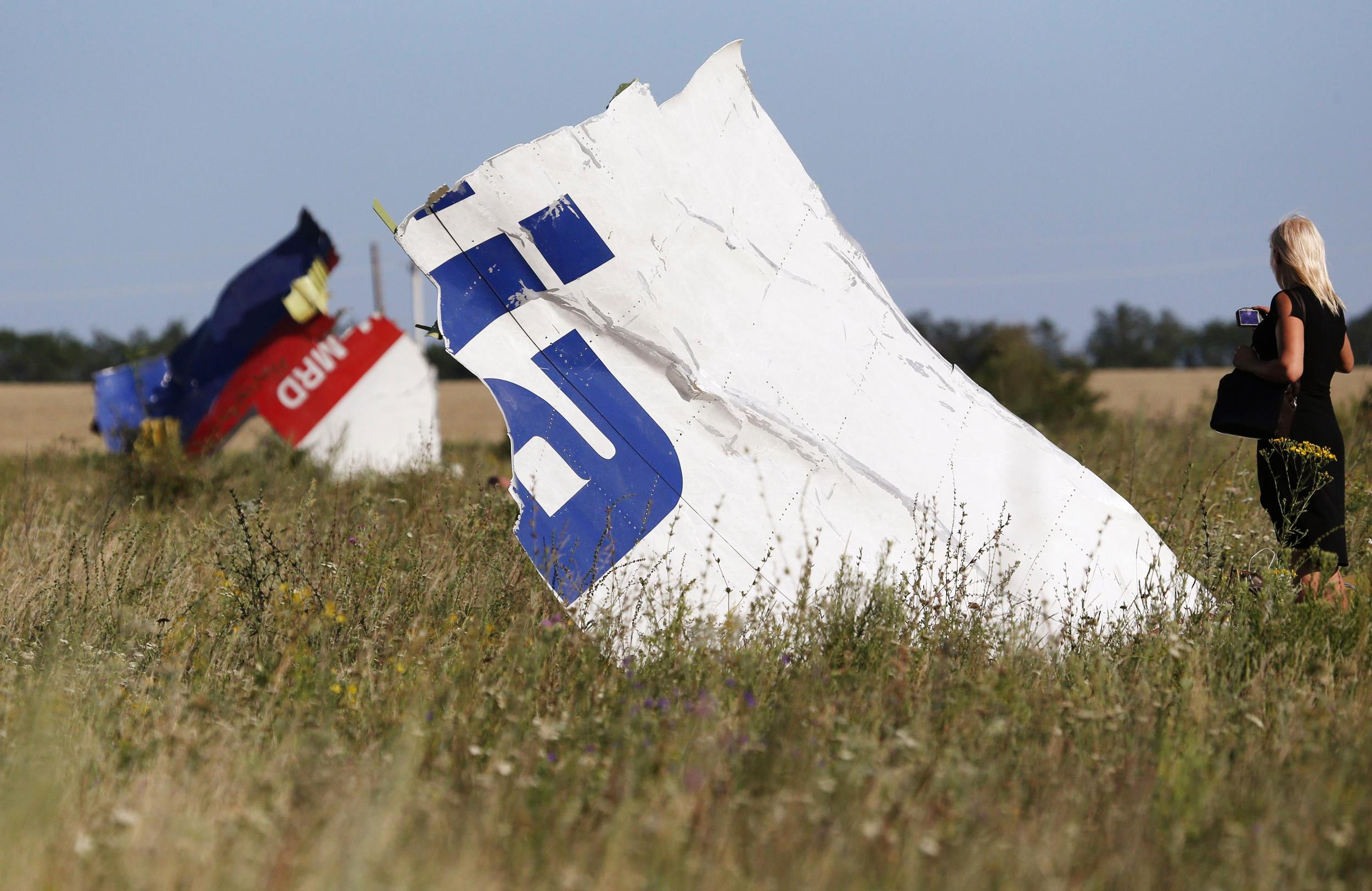 Image: A woman takes a photograph of wreckage at the crash site of Malaysia Airlines Flight MH17 near the village of Hrabove (Grabovo)
