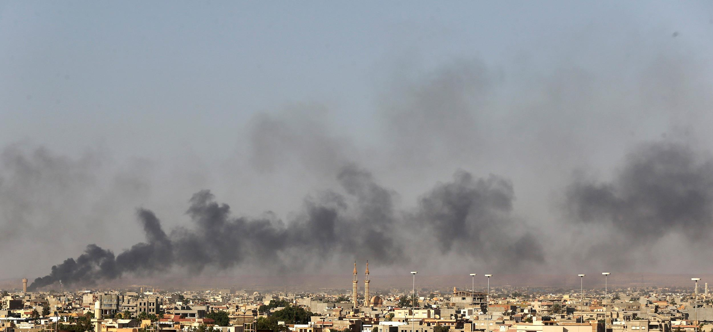 Image: Black plumes of smoke is seen in the vicinity of Camp Thunderbolt, after clashes between militants, former rebel fighters and government forces in Benghazi