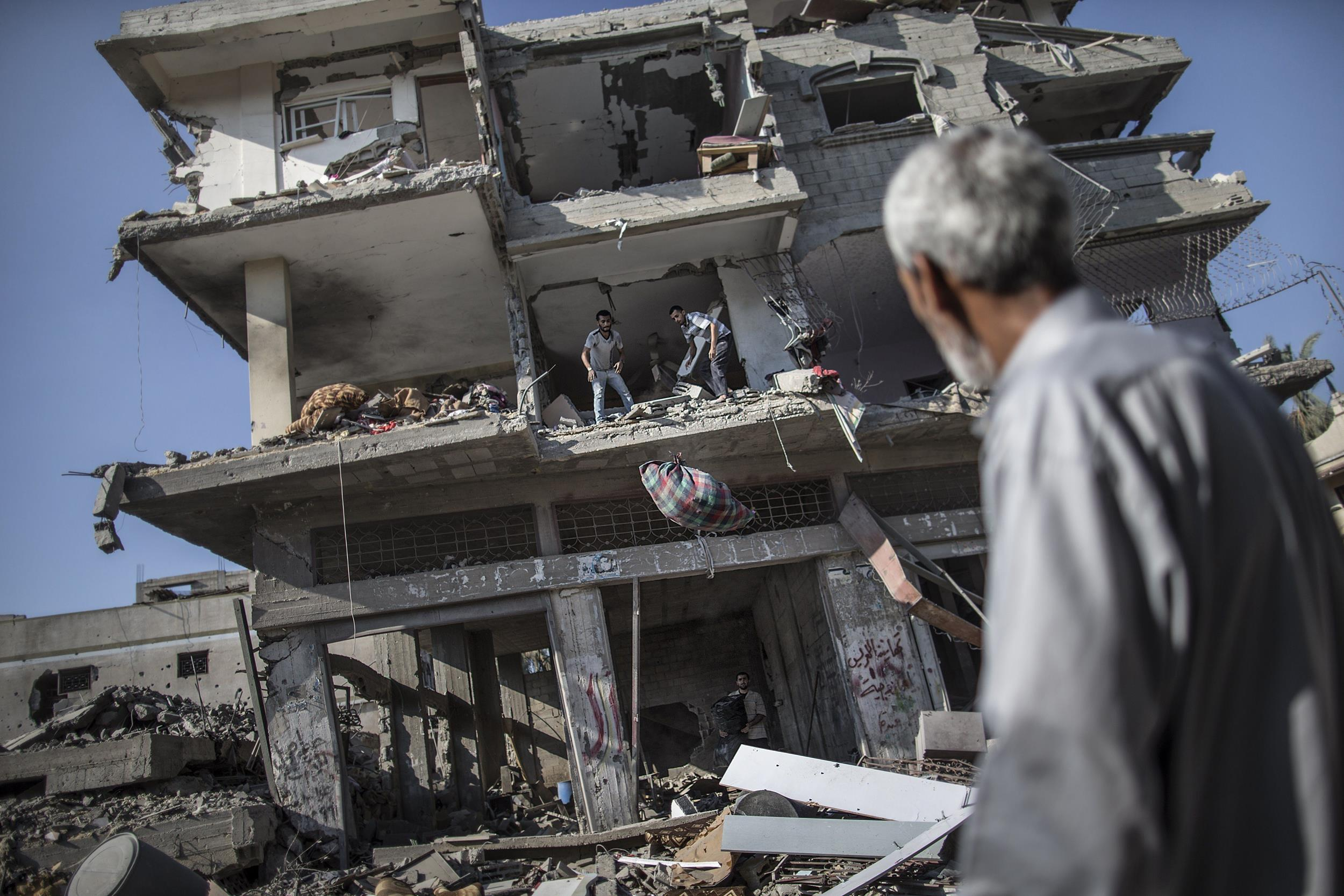Image: A Palestinian looks at people collecting items and belongings they found in the rubble of a destroyed building