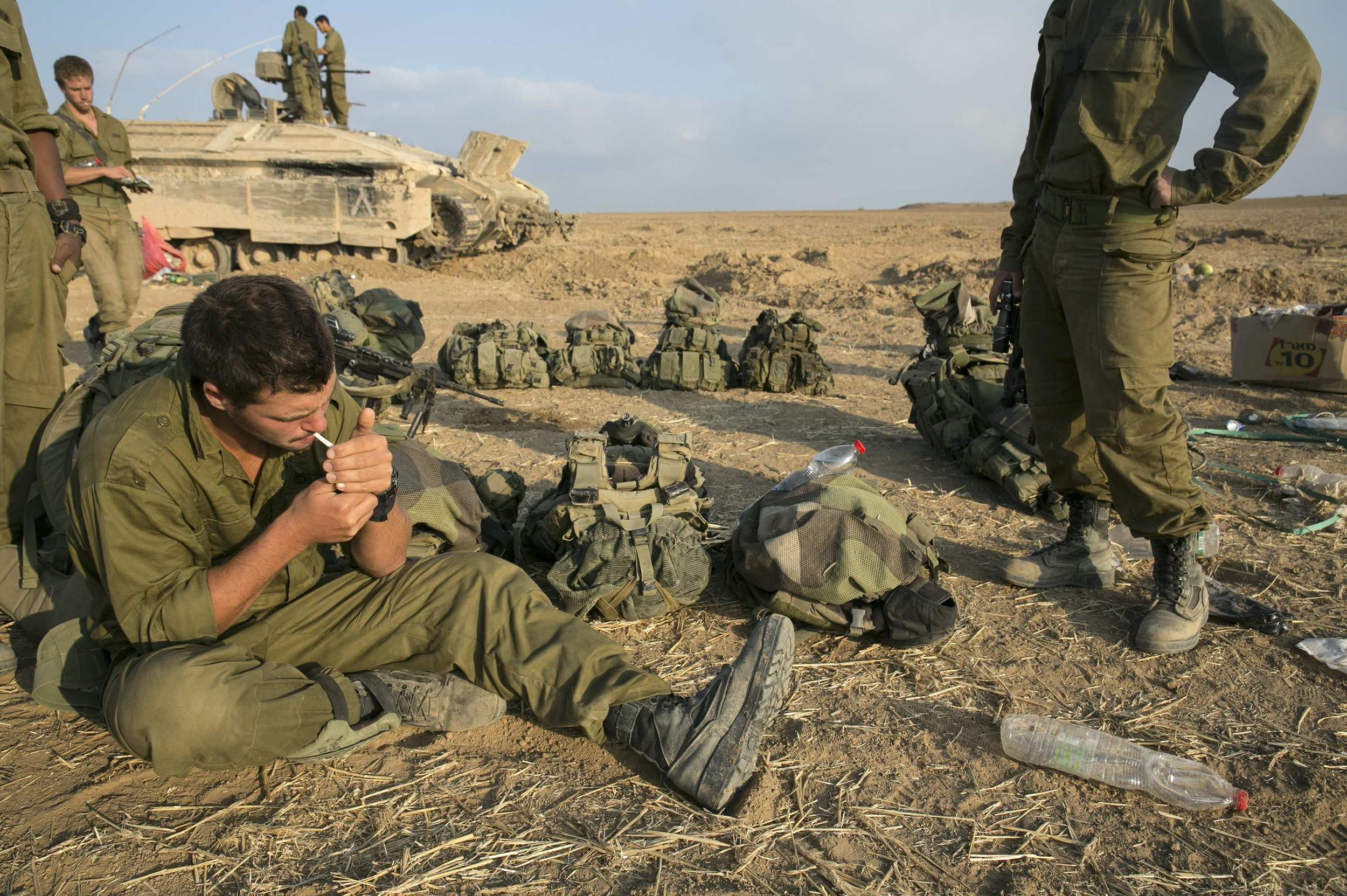 Image: An Israeli soldier smokes a cigarette after crossing back into Israel from Gaza