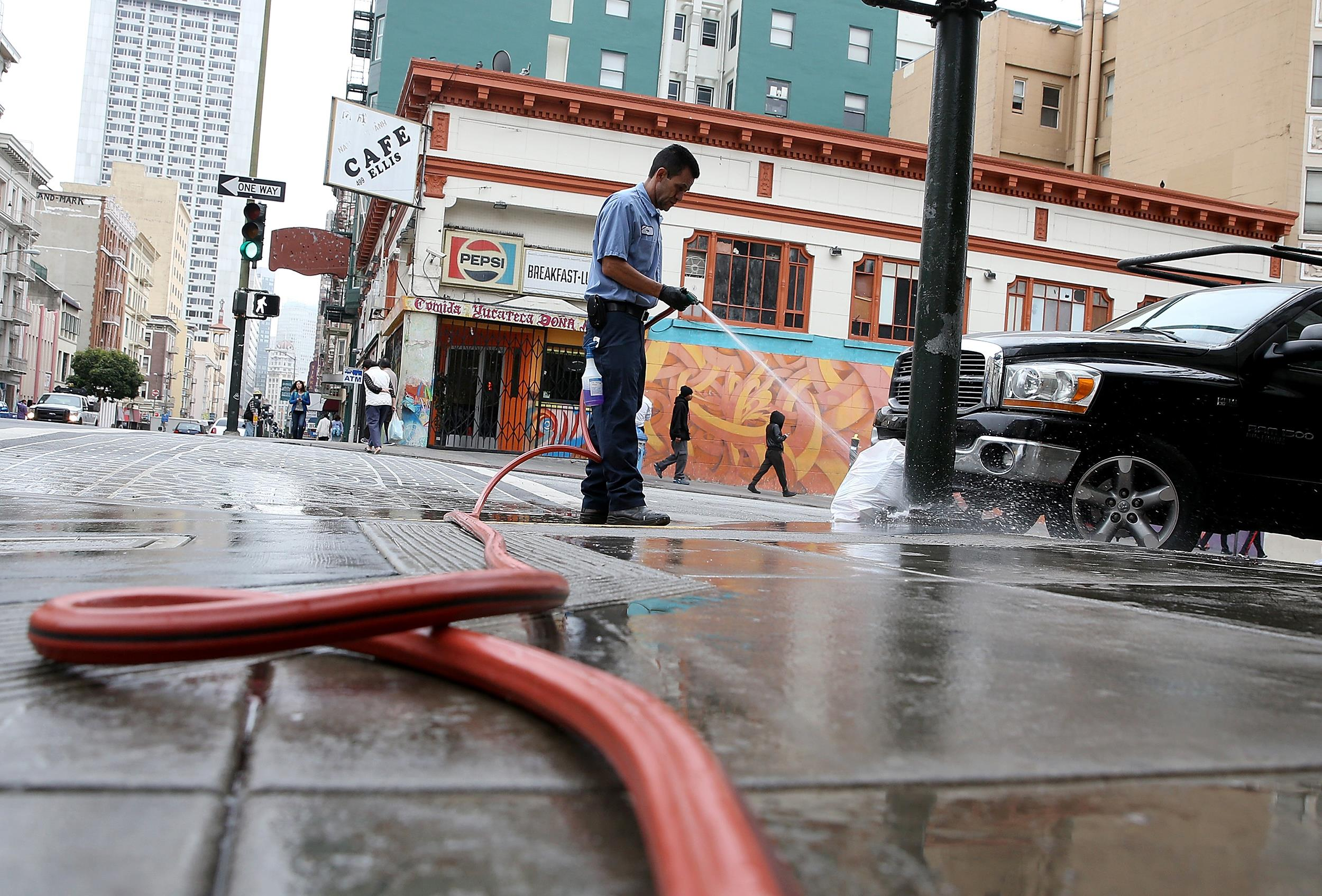 Image: A worker uses a hose to wash the sidewalk in front of a residential hotel on July 15 in San Francisco, Calif.