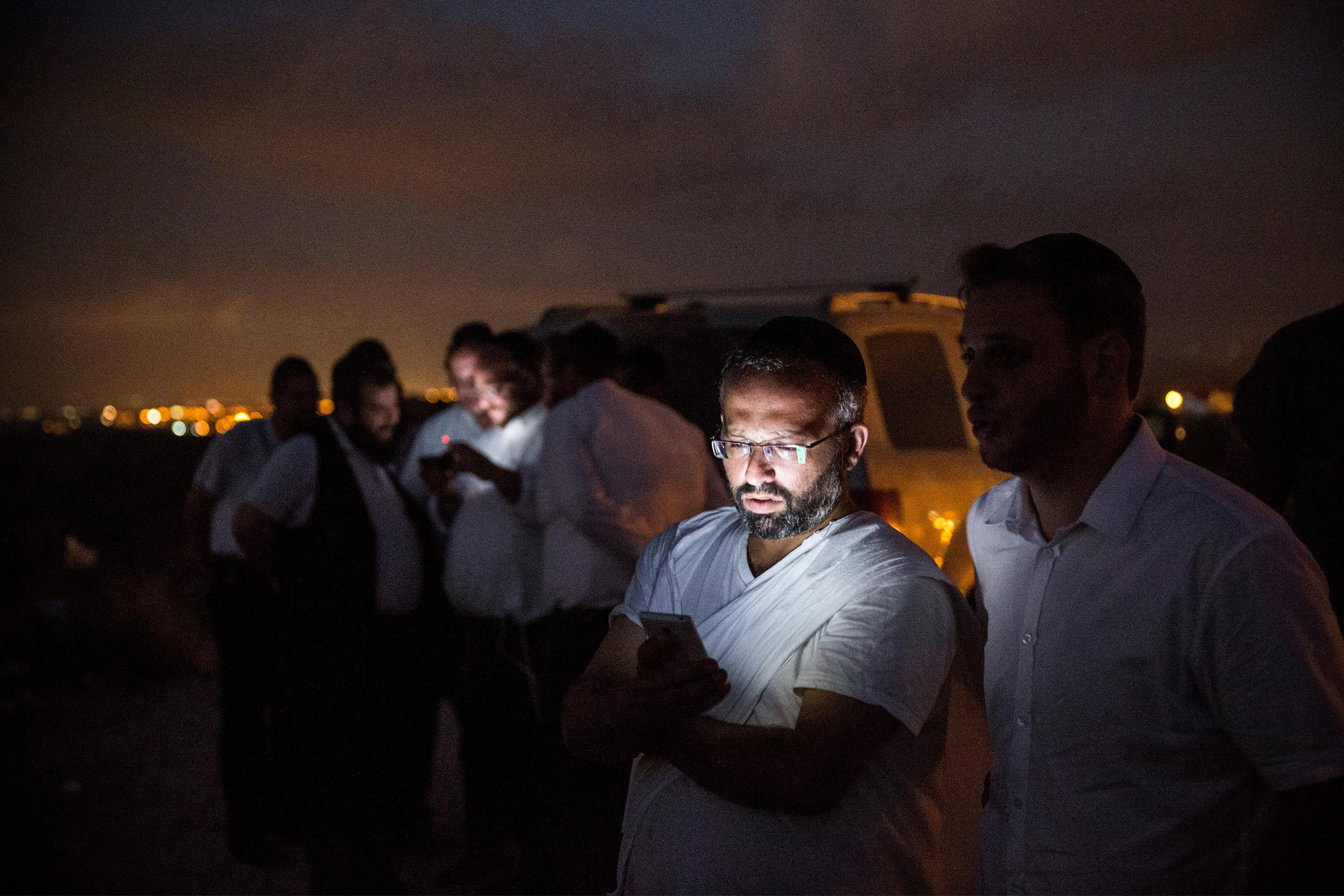 Image: Israelis check their cellphones while waiting for outgoing rocket fire or Israeli airstrikes from a hill overlooking the Gaza Strip