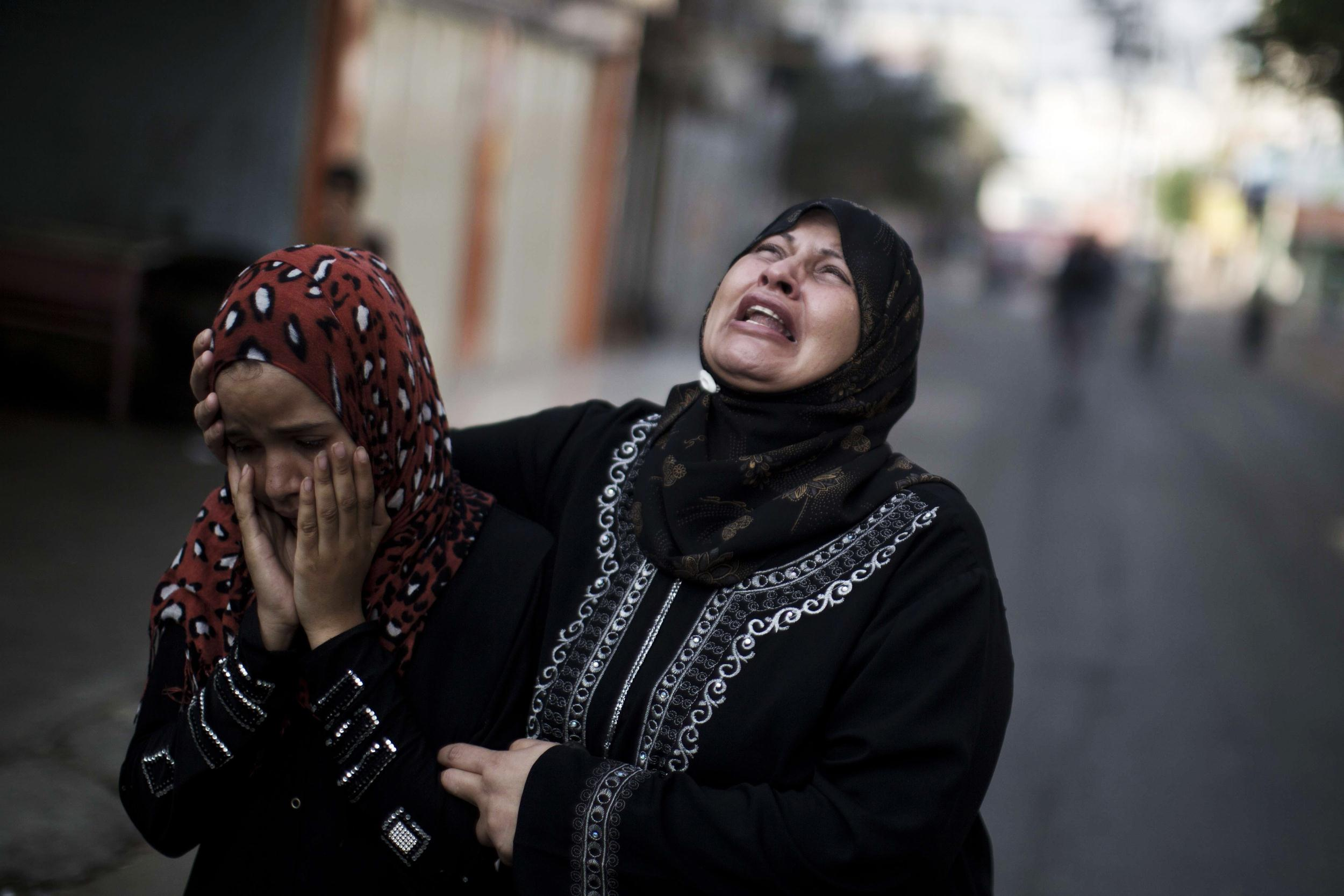 Image: Palestinians who lost relatives in an Israeli strike mourn outside the Kamal Edwin hospital
