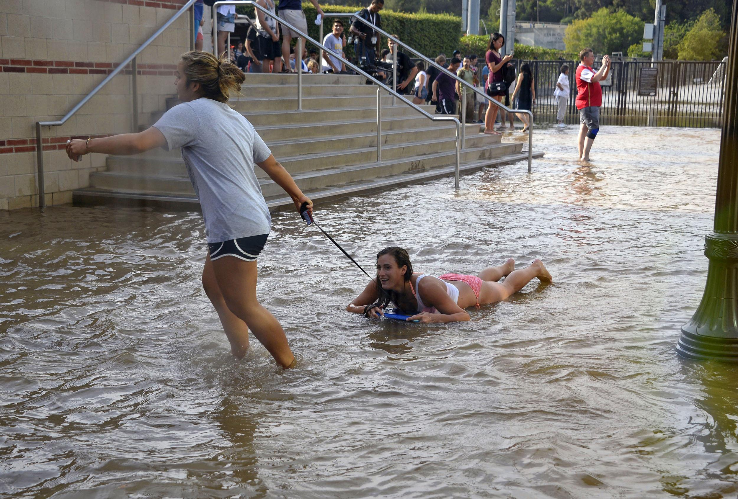 Image: One woman pulls another on a body board through water on the quad of UCLA after flooding from a broken 30-inch water main on July 29.