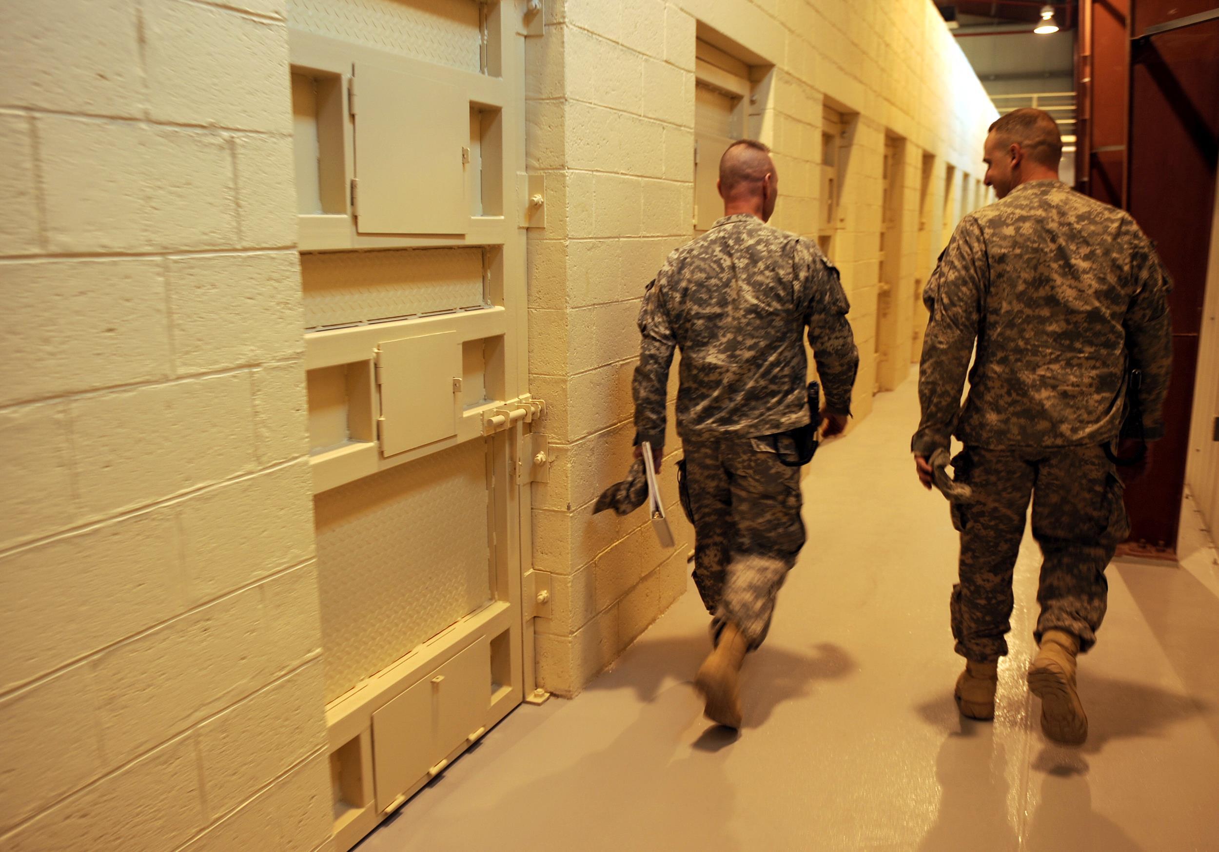 Image: U.S. soldiers walk past prison cells during a media tour of Bagram prison, north of Kabu