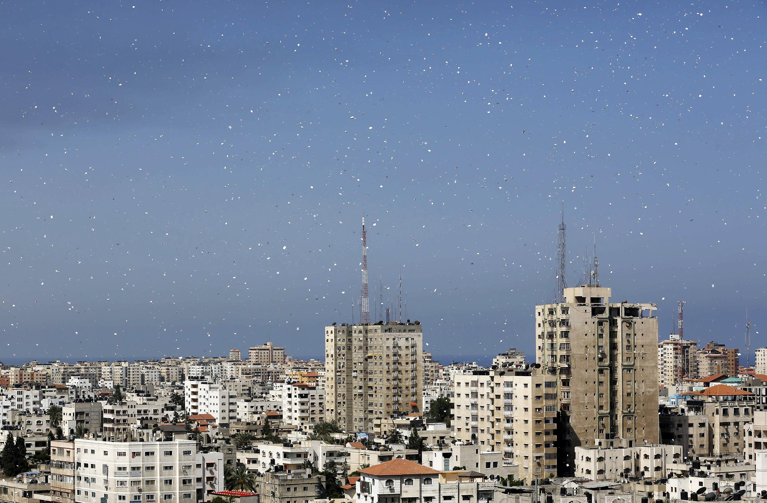 Image: Fliers are dropped over Gaza City by the Israeli army urging residents to evacuate their homes