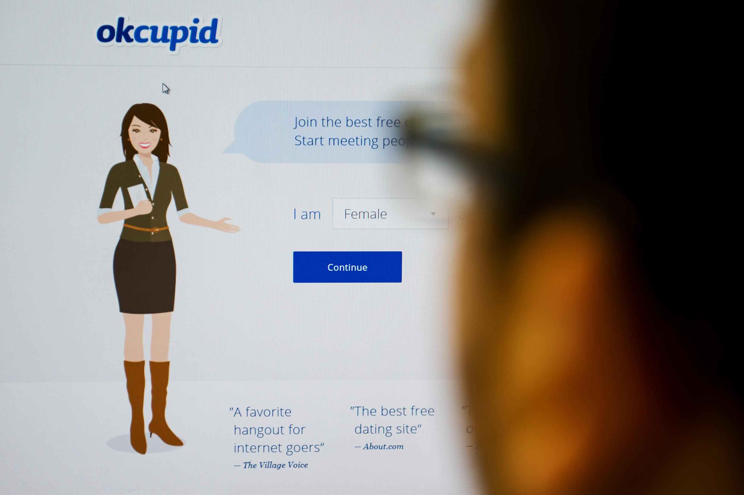 Image: In a photo illustration, a person looks at the OkCupid website.