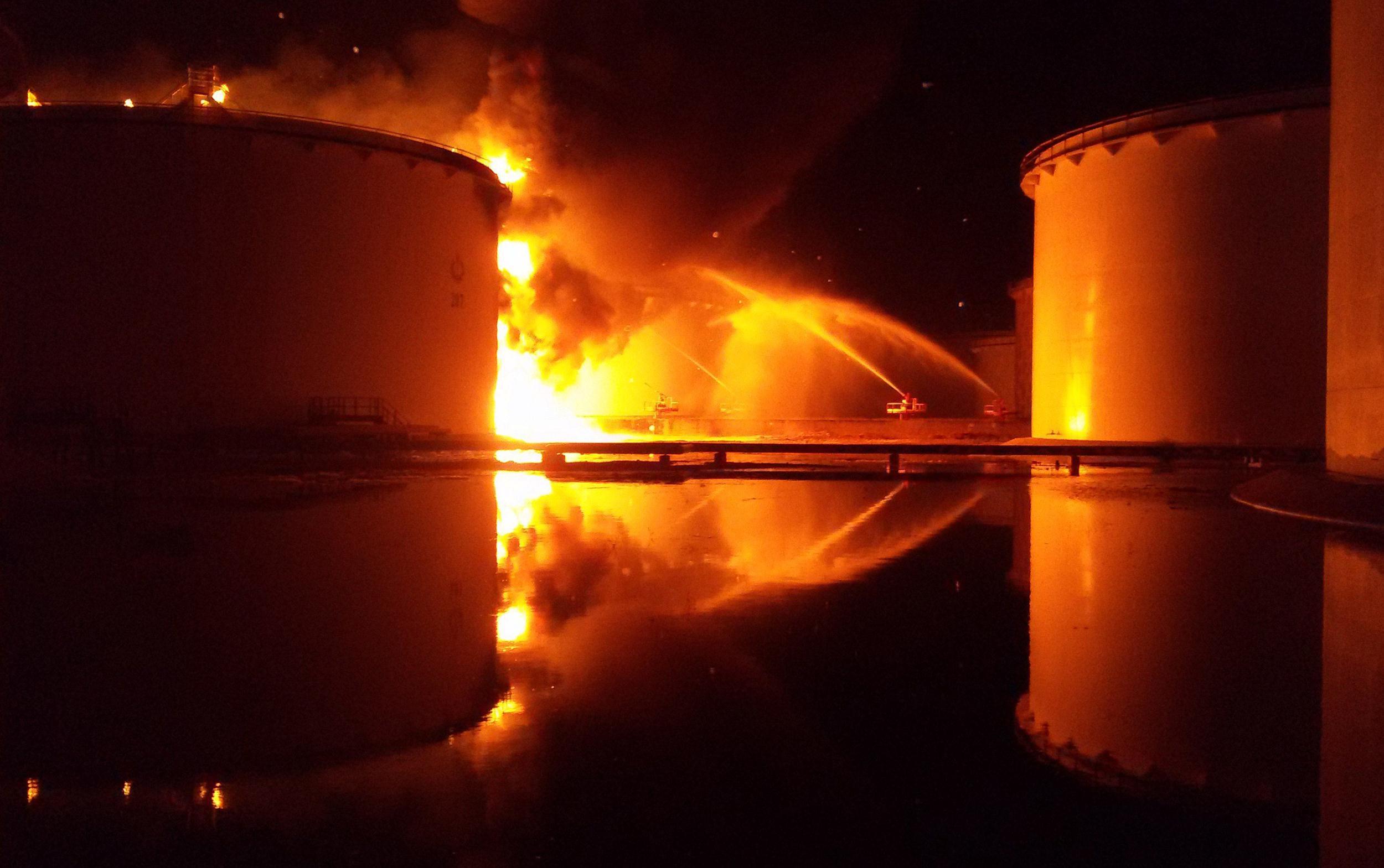 Image: Libyan firefighters dousing a huge blaze at an oil tank