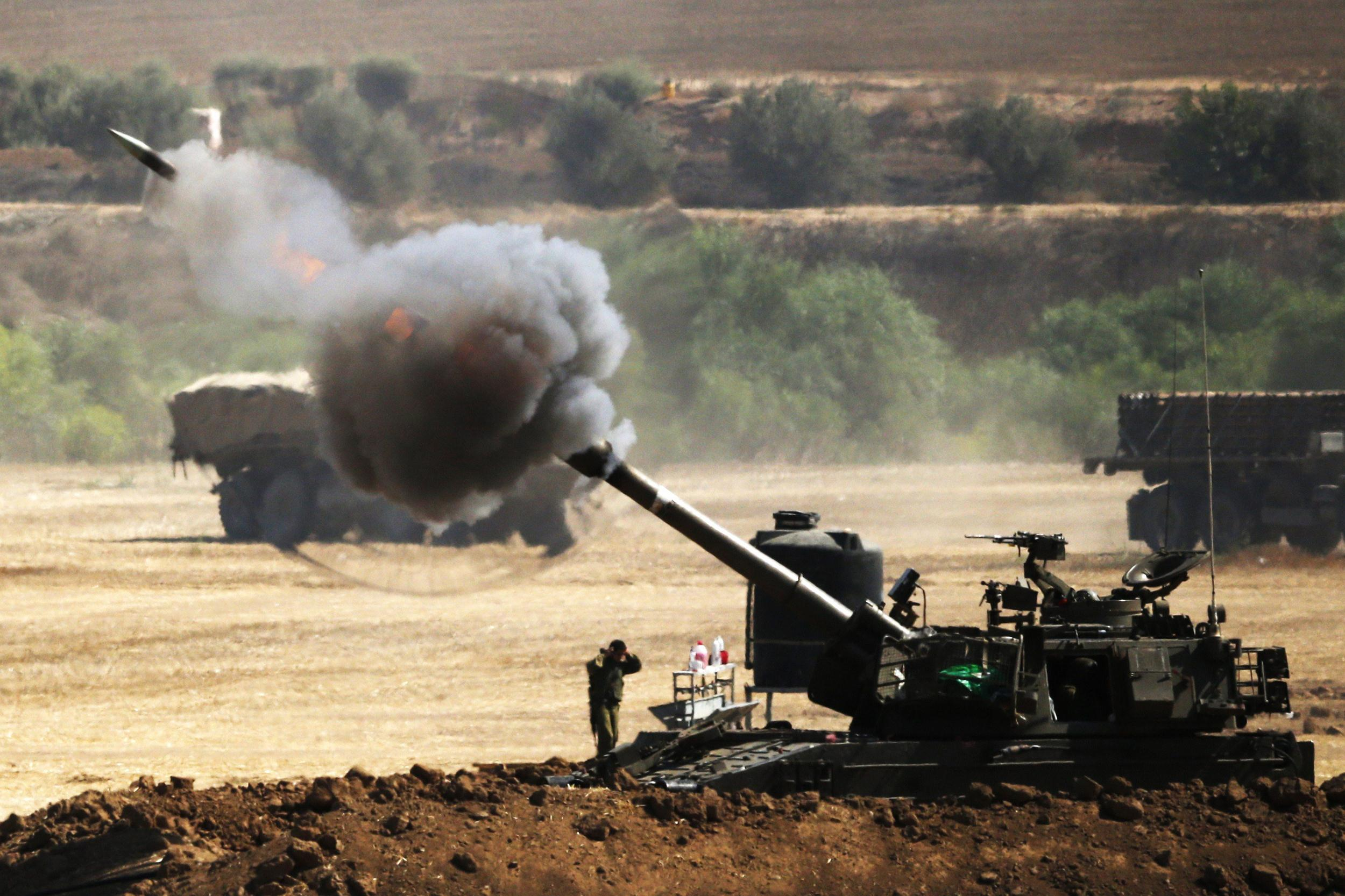 Image: An Israeli artillery gun fires a 155mm shell towards targets from their position near Israel's border with the Gaza Strip