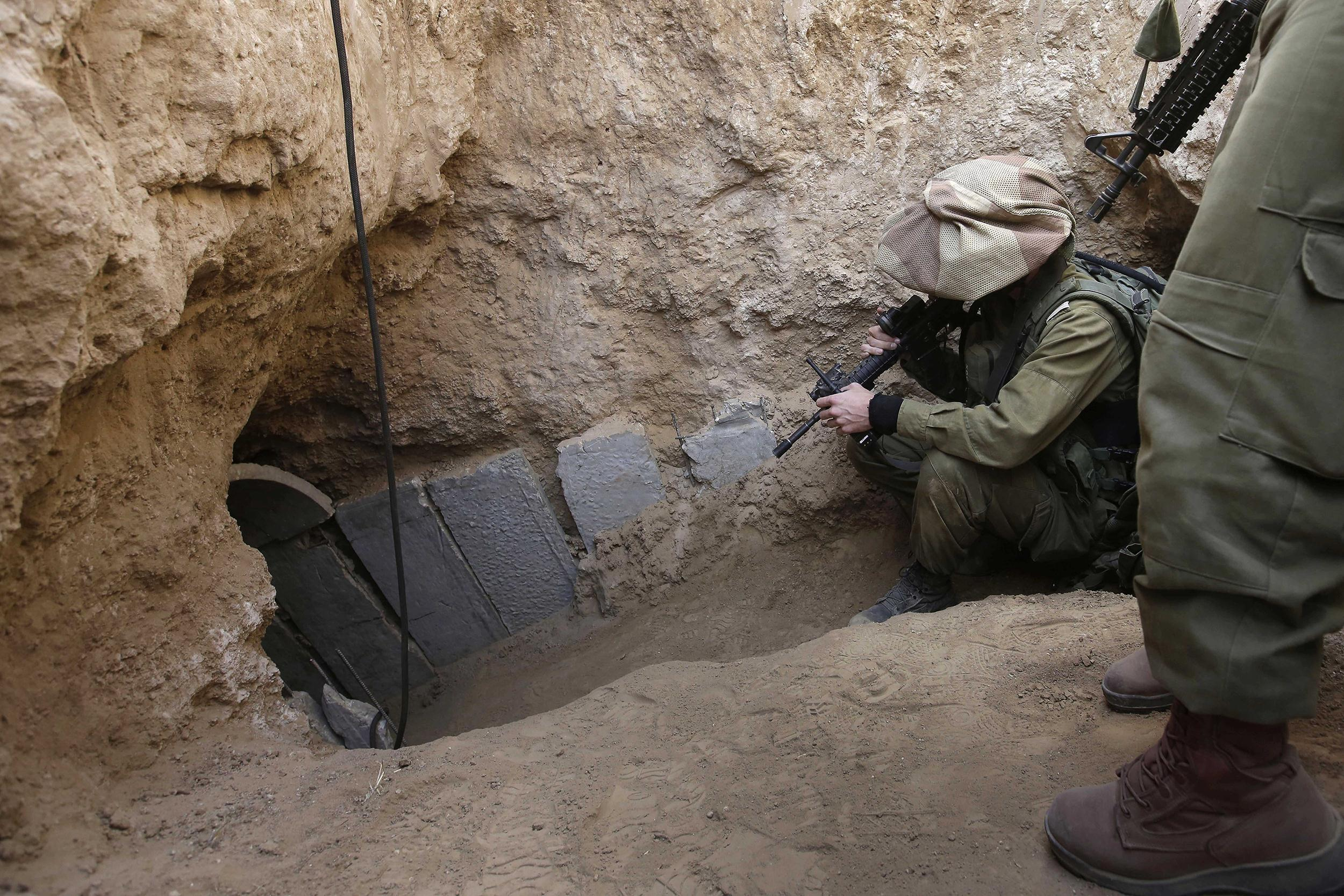 Image: Israeli soldiers enter a tunnel discovered near the Israel Gaza border on Oct. 13, 2013.
