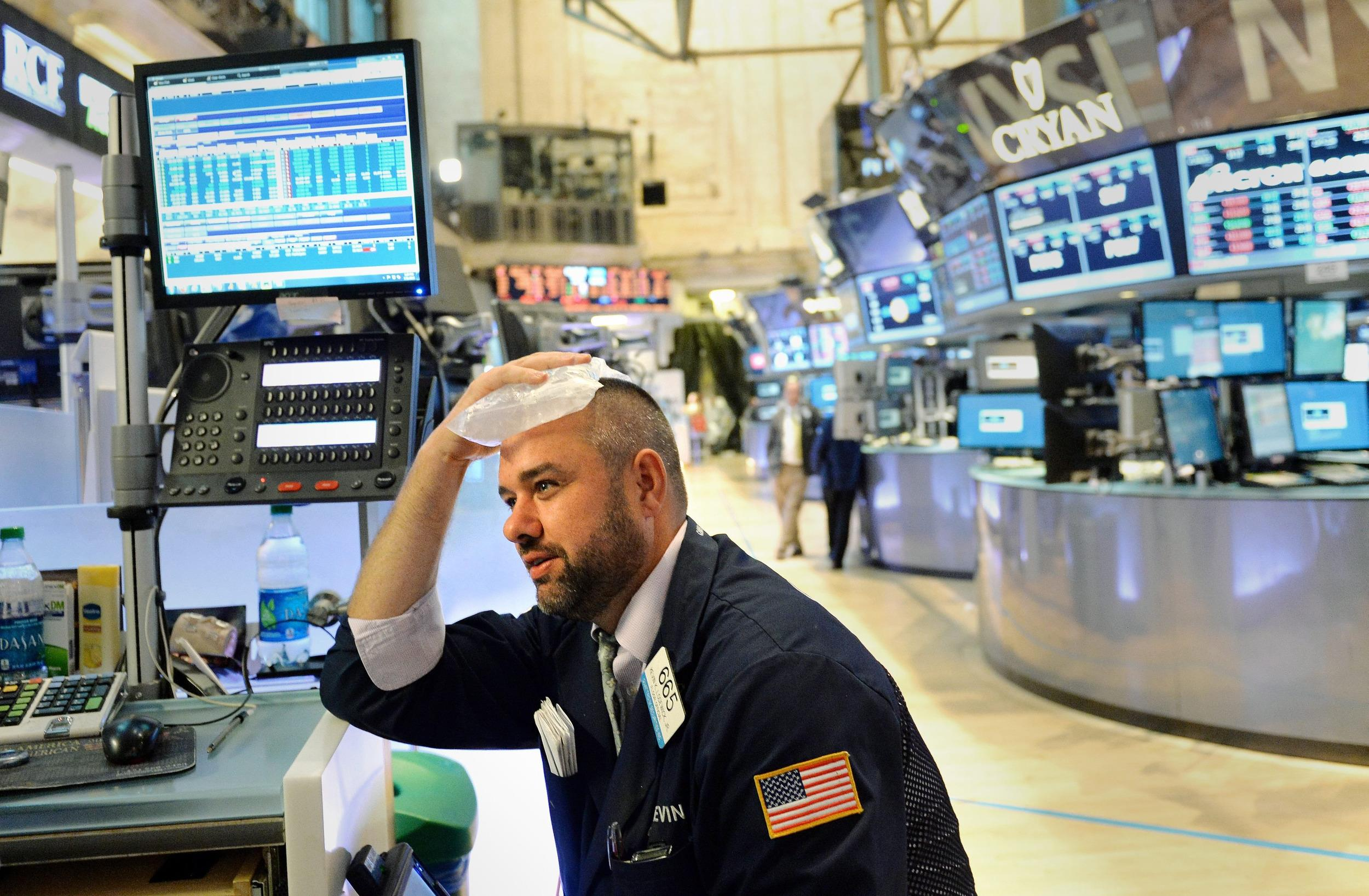 It's enough to give anyone a headache! A trader on the New York Stock Exchange reacted as stocks fell over 1 percent on Thursday.