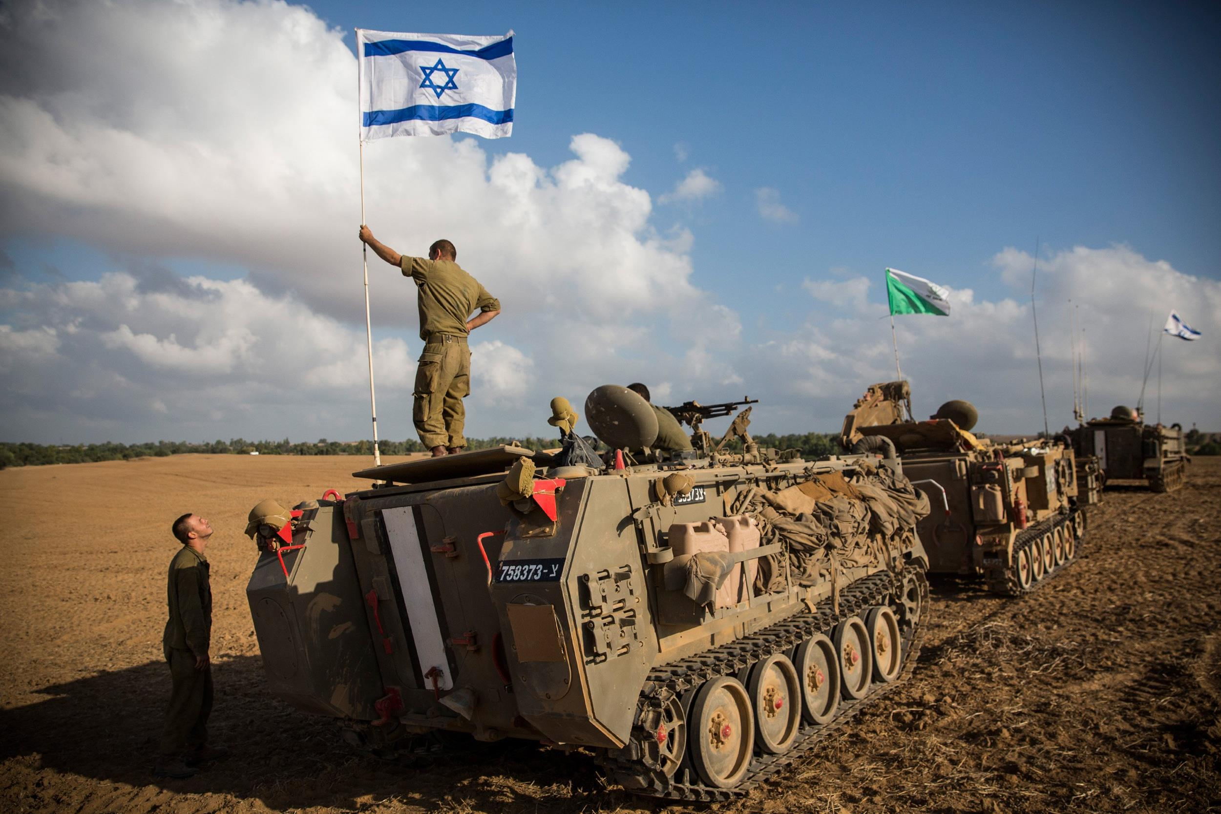 Image: An Israeli soldier stands on top of an armored personnel carrier near the Israeli-Gaza border on July 15, 2014 near Sderot, Israel.