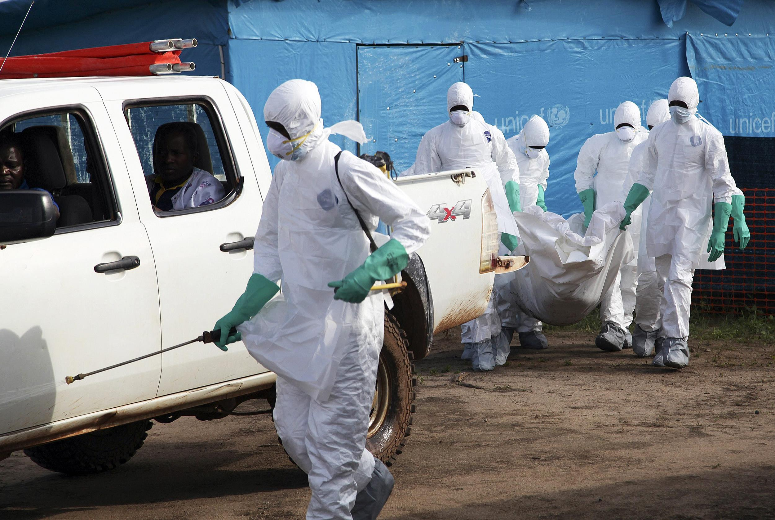 Image: Liberian health workers in protective gear prepare to bury a woman who died of the Ebola virus from the isolation unit in Foya, Lofa County, Liberia, July 2.