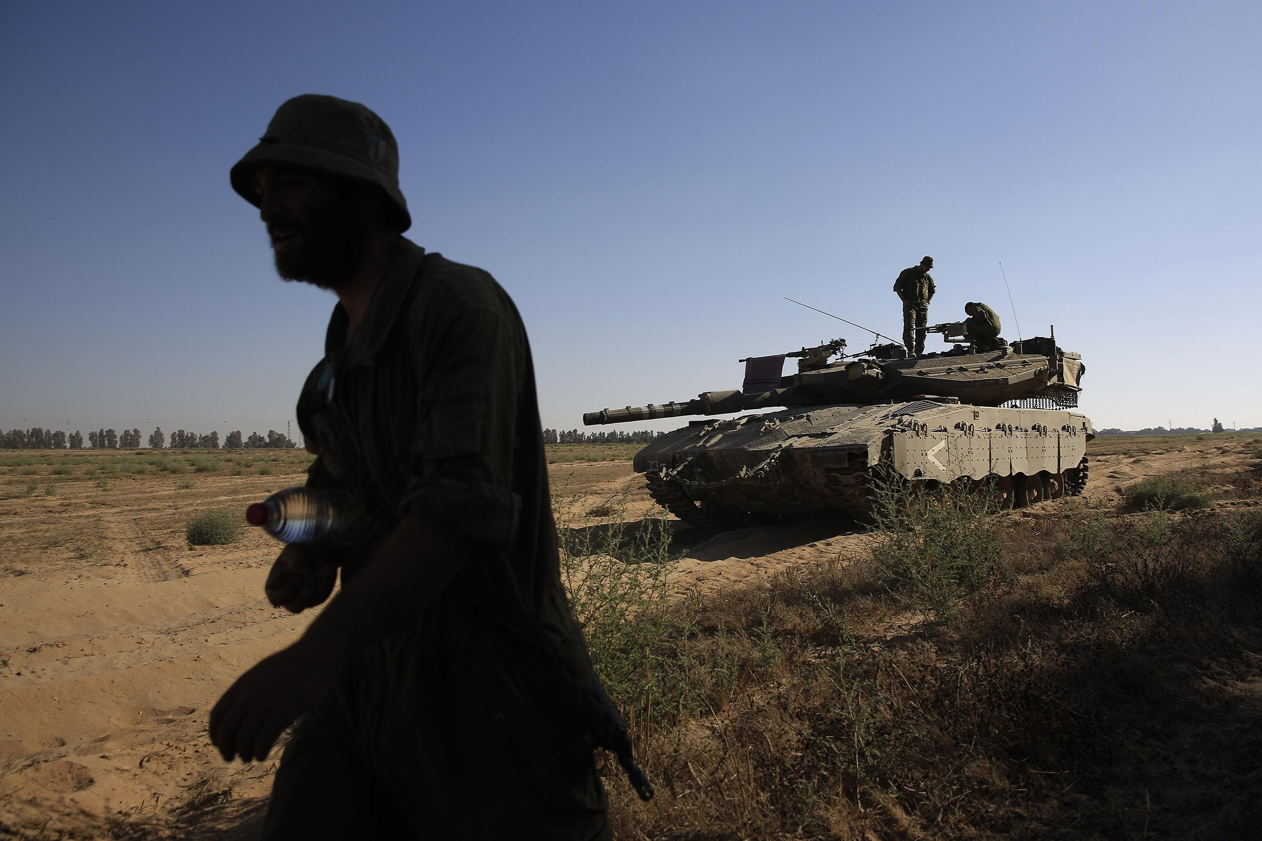 Image: An Israeli soldier walks near a tank in a staging area near the Israel Gaza border,