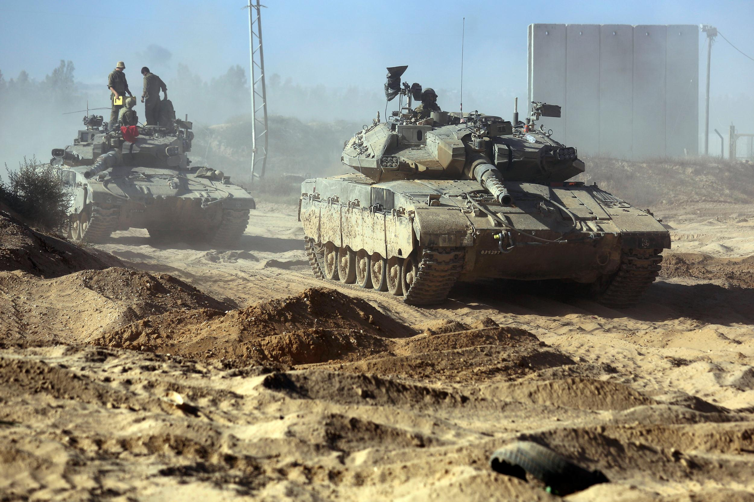 Image: Israeli soldiers stand on top of a tank in a staging area near the Israel Gaza border