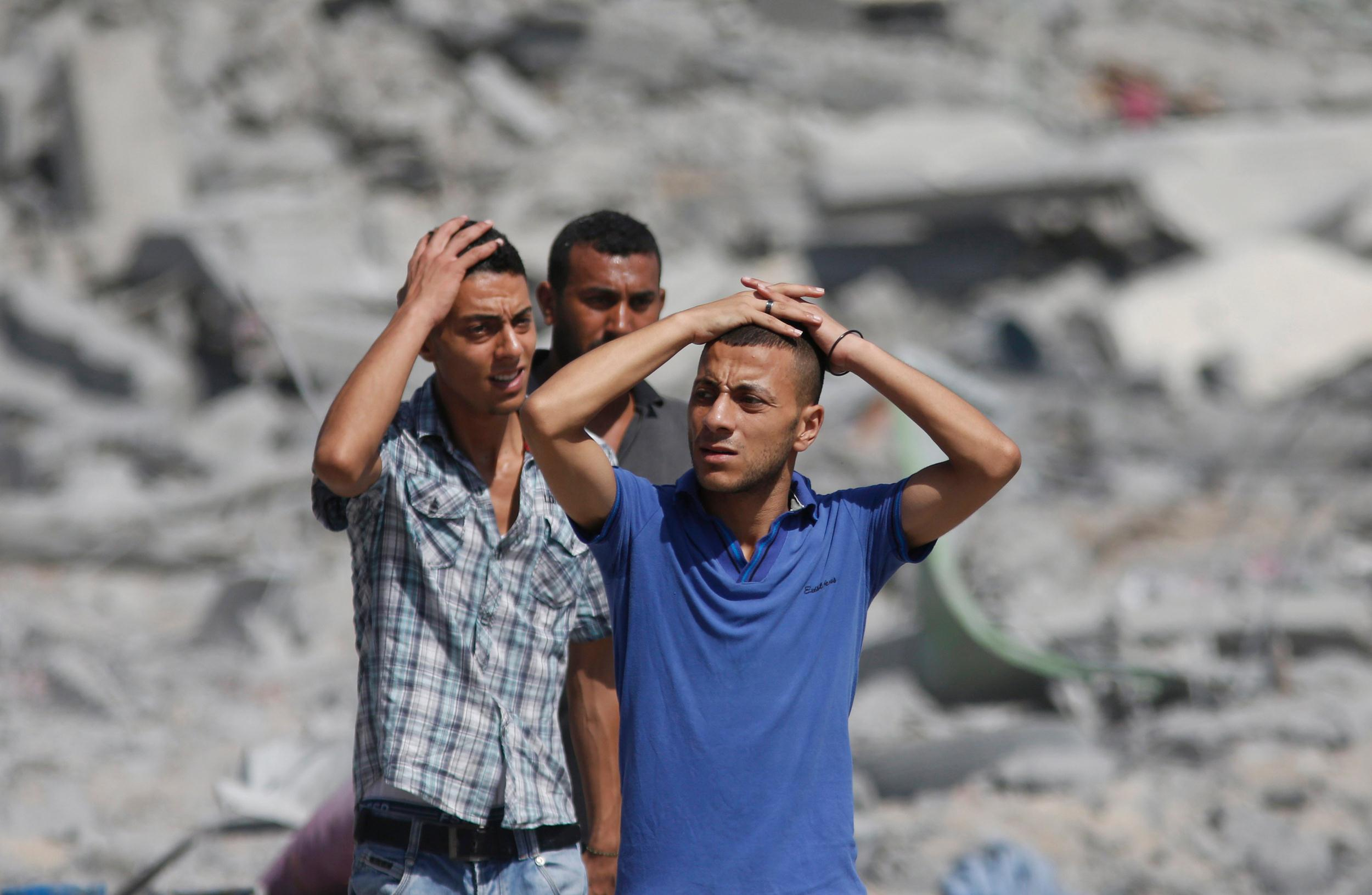 Image: Palestinians react as they walk in the heavily bombed town of Beit Hanoun