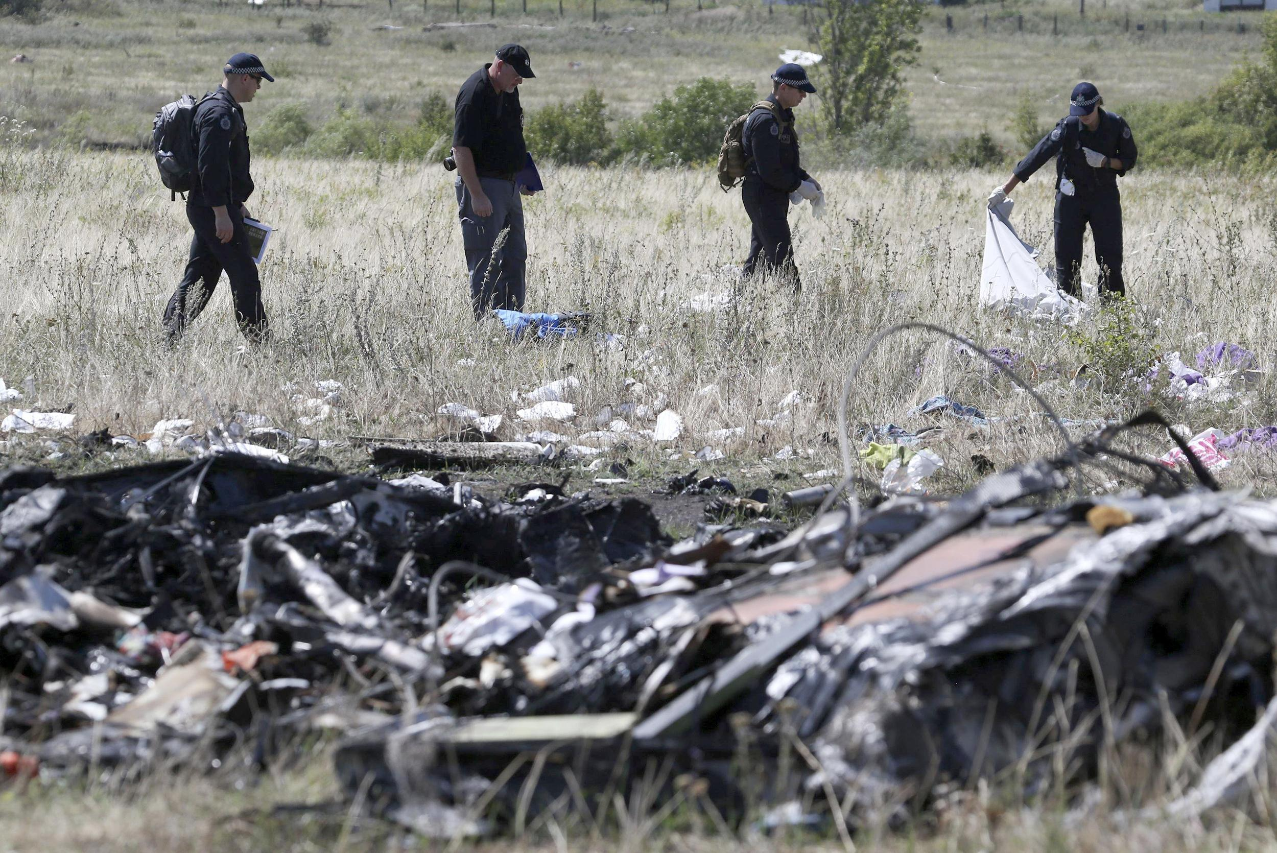 Image: Members of a group of international experts inspect the territory at the site where the downed Malaysia Airlines Flight MH17 crashed in Donetsk region