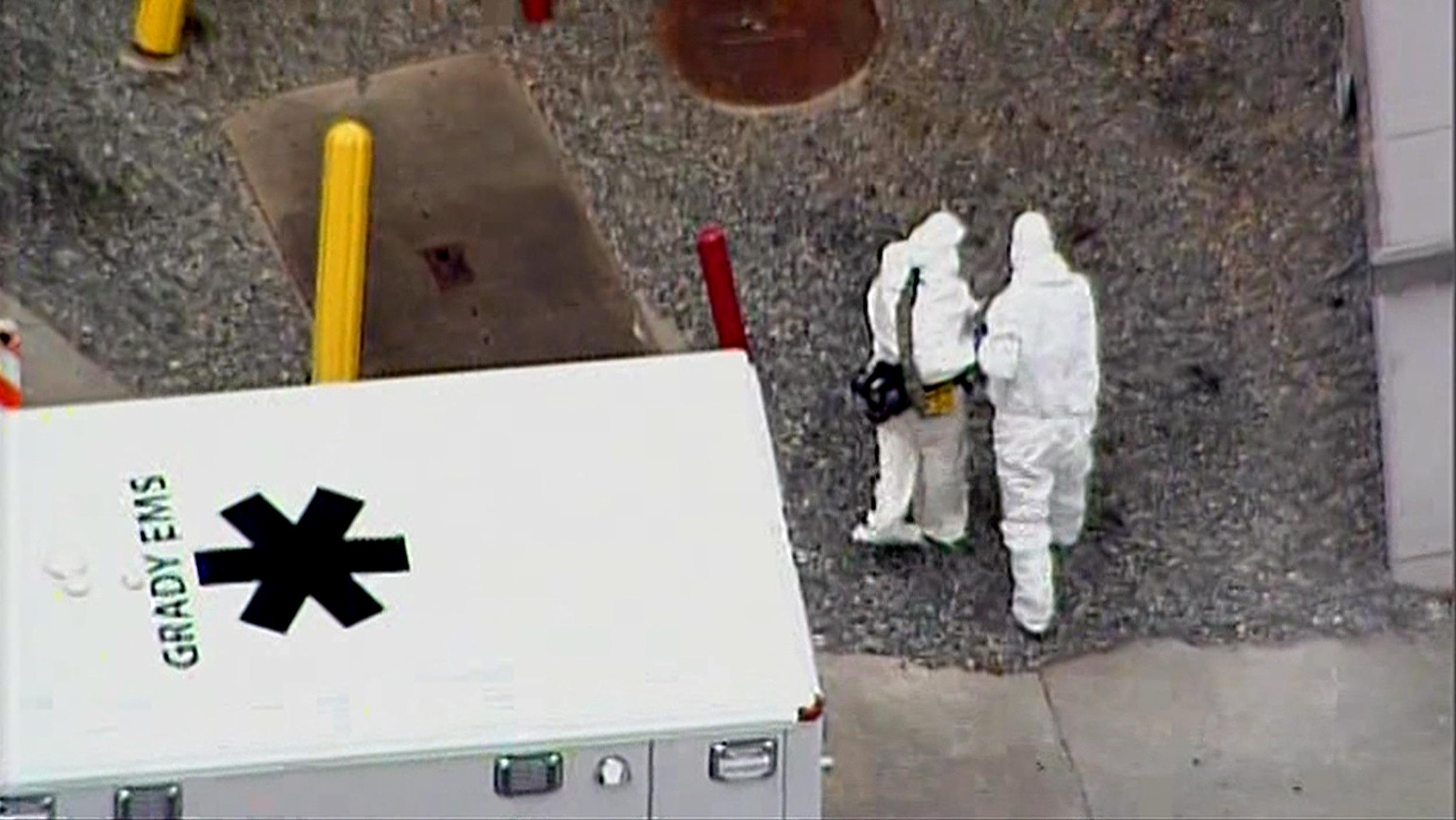 Image: Dr. Kent Brantly and a man in a protective suit leave an ambulance at Emory University Hospital