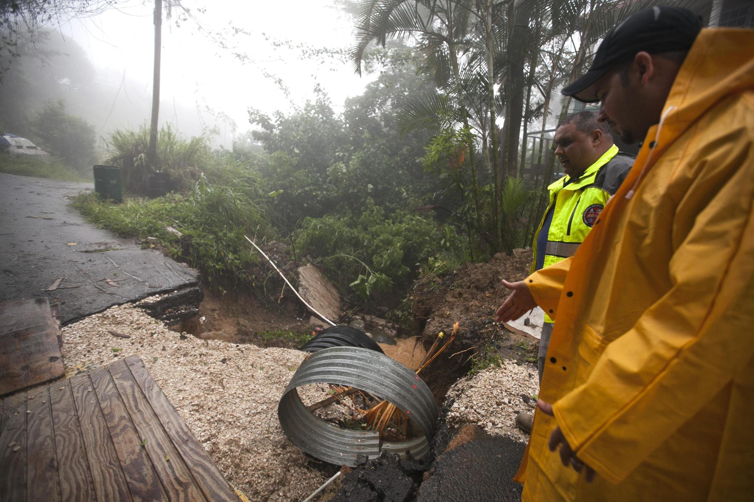 Image: Villalba Mayor Ortiz and Bonilla, director of the Emergency Management Agency, stop to check damages affecting improvements to the aqueduct infrastructure in the sector after heavy rain, in Aceituna town