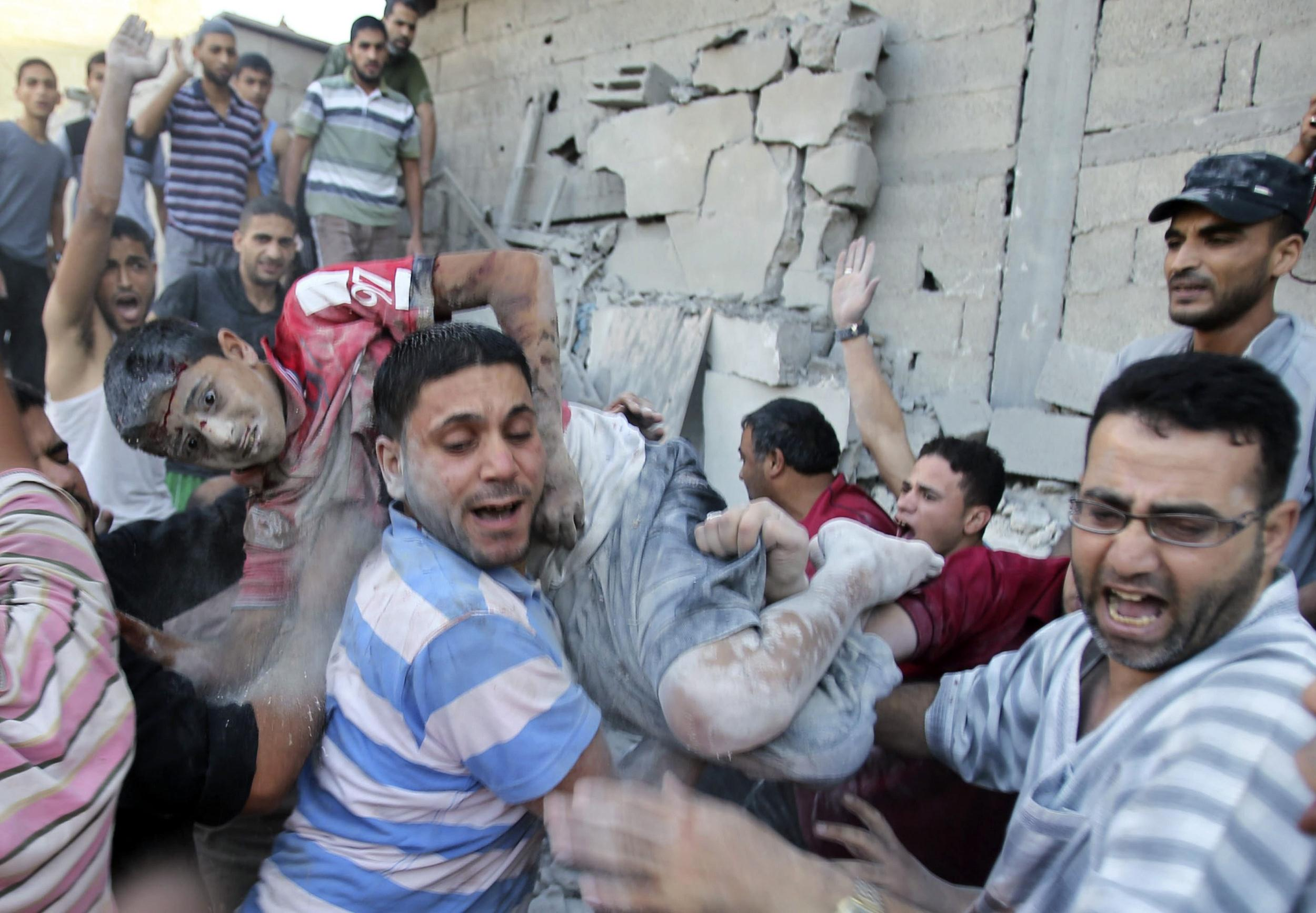 Image: Palestinians carry a wounded a boy who was evacuated from under the rubble of a house in Rafah