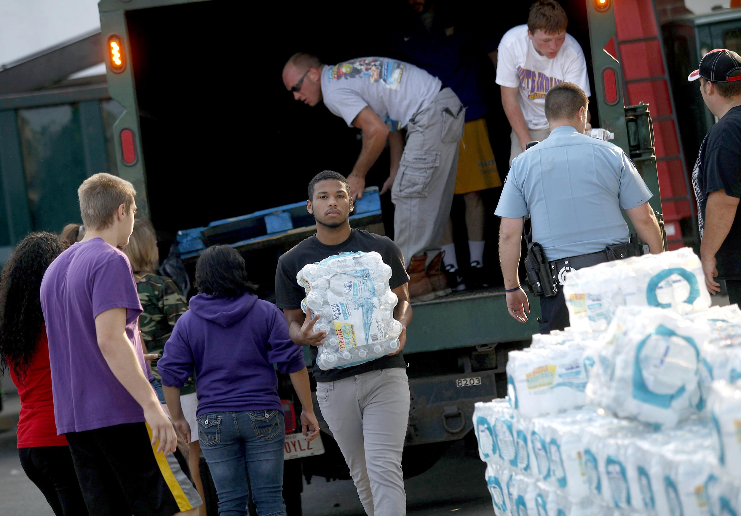 Image: Volunteers unload drinking water from a truck outside Waite High School in Toledo,
