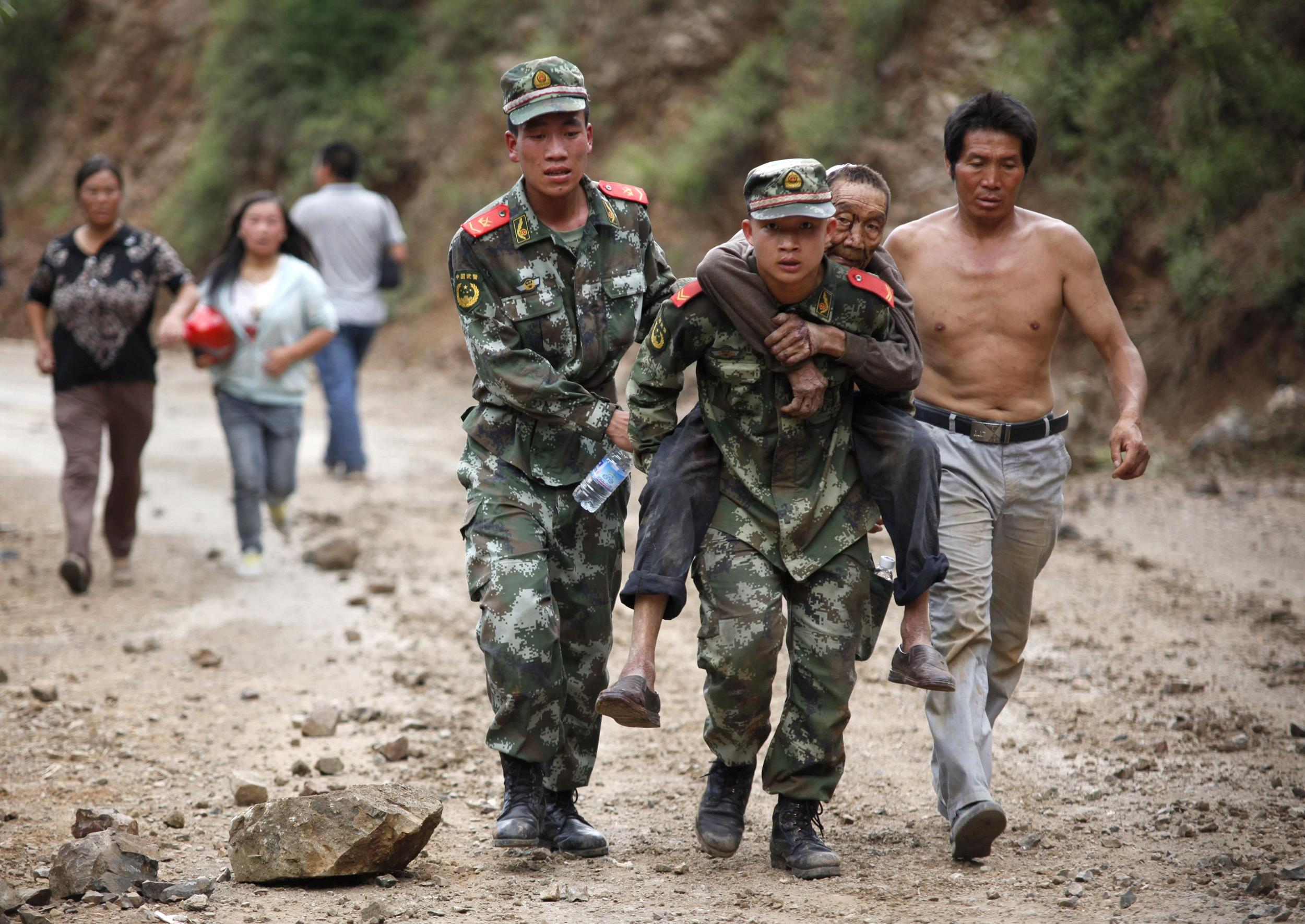Image: Chinese rescuers carry an injuried resident after an earthquake