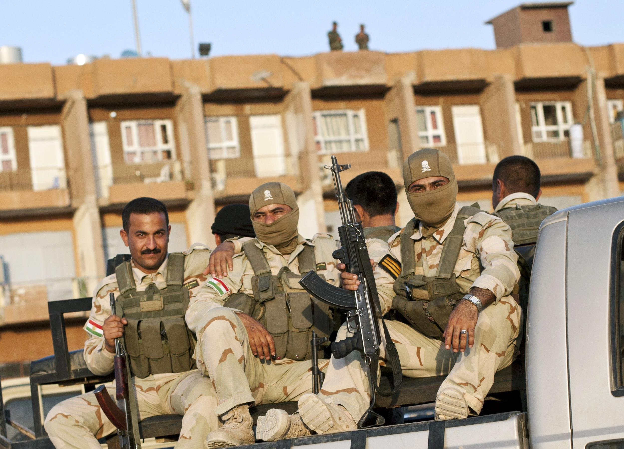 Image: Iraqi Kurdish forces sit at the back of a truck at an operating base in Iraq's Diyala province