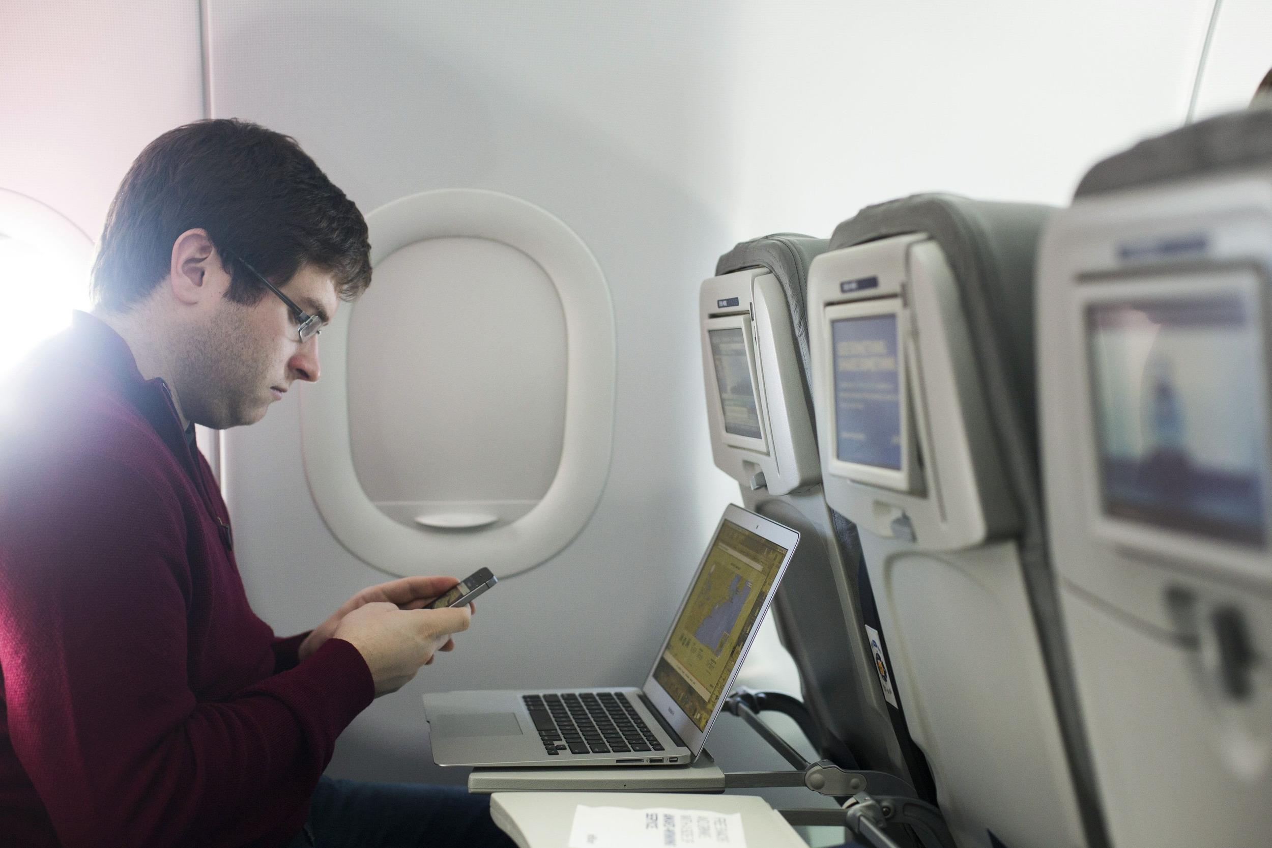 Image: A man uses his mobile phone and laptop to test a new high speed inflight Internet service named Fli-Fi while on a special JetBlue media flight out of John F. Kennedy International Airport in New York