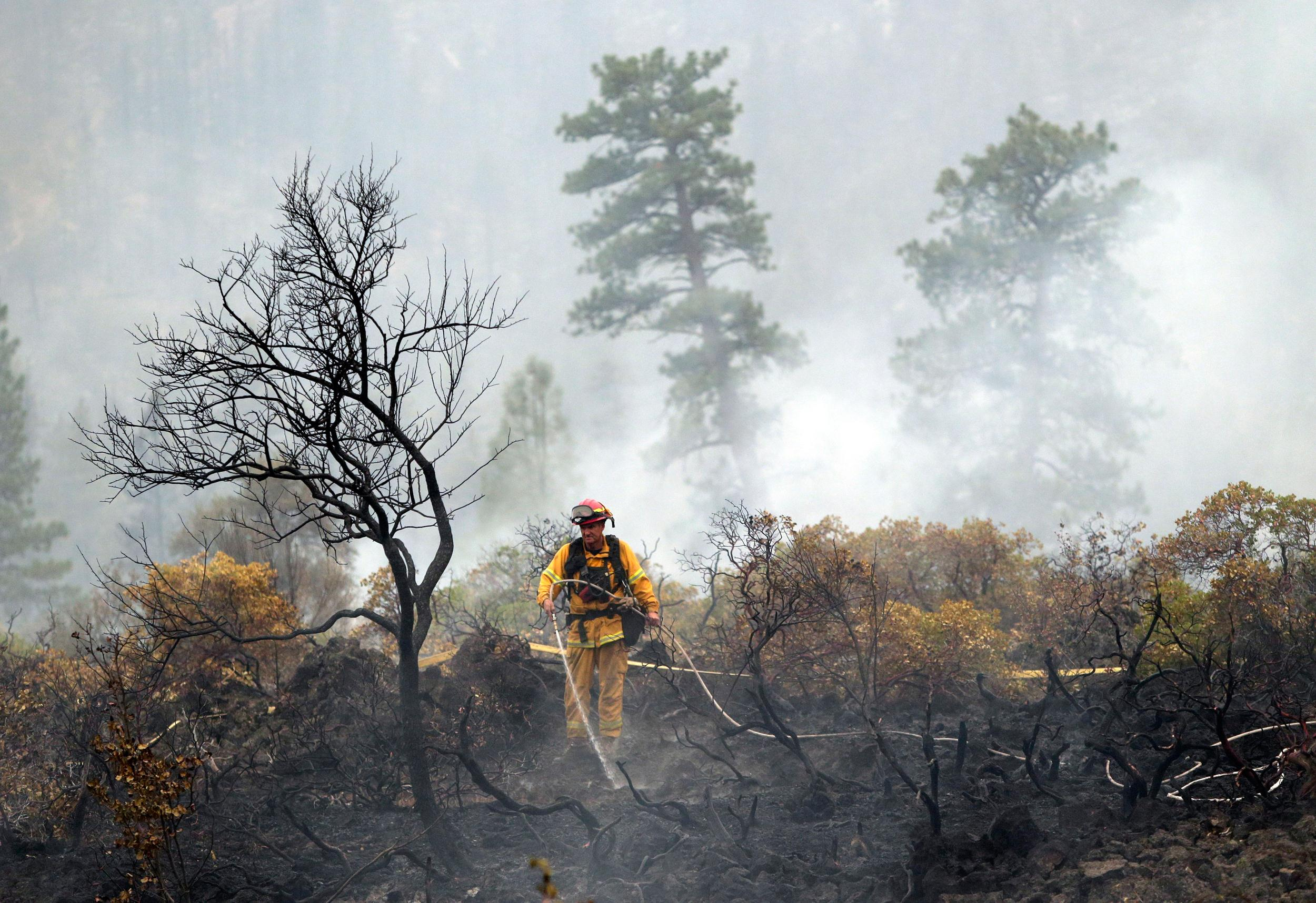 Image: A firefighter with the Anderson, Calif., Fire Protection District douses hot spots left behind by the Eiler Fire