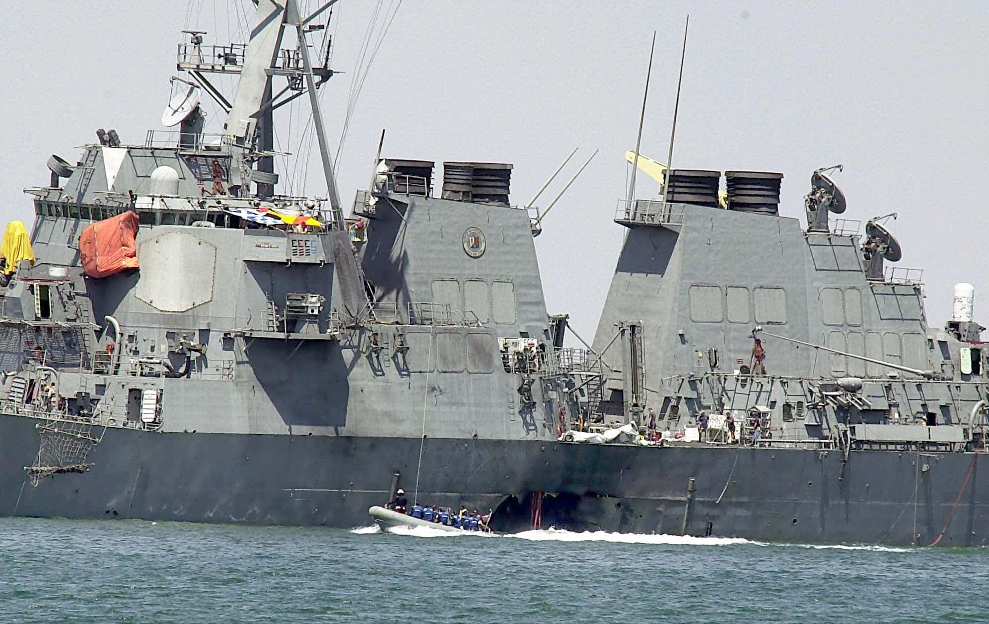 Image: Investigators in a speed boat examine the hull of the USS Cole at the Yemeni port of Aden