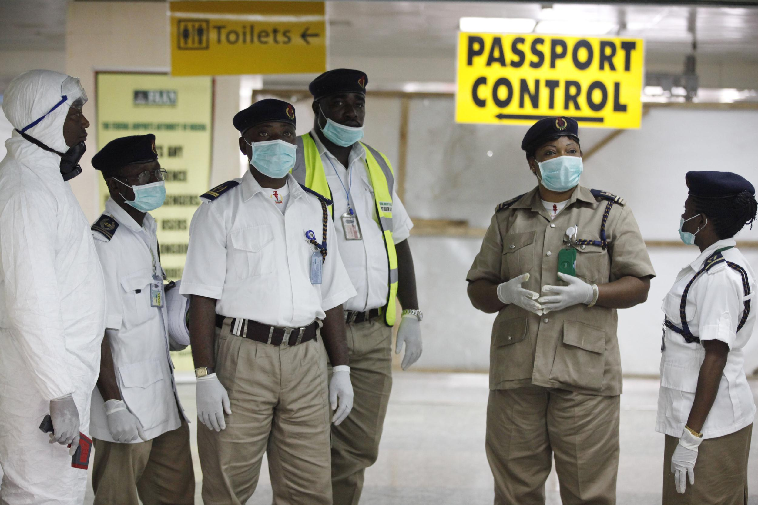 Image: Nigeria health officials wait to screen passengers at the airport in Lagos.