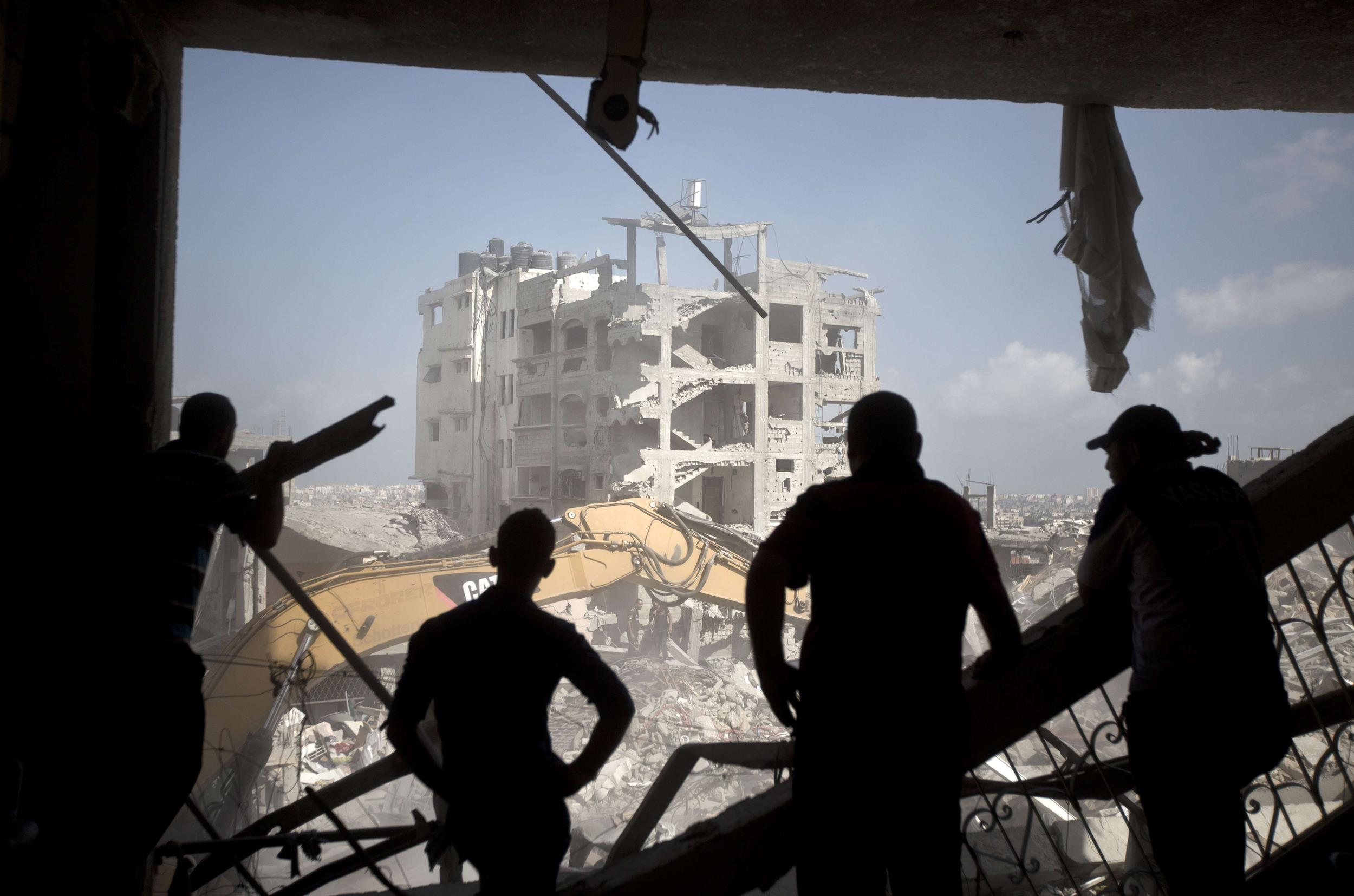 Image: Palestinian men inspect destruction in part of Gaza City's al-Tufah neighborhood