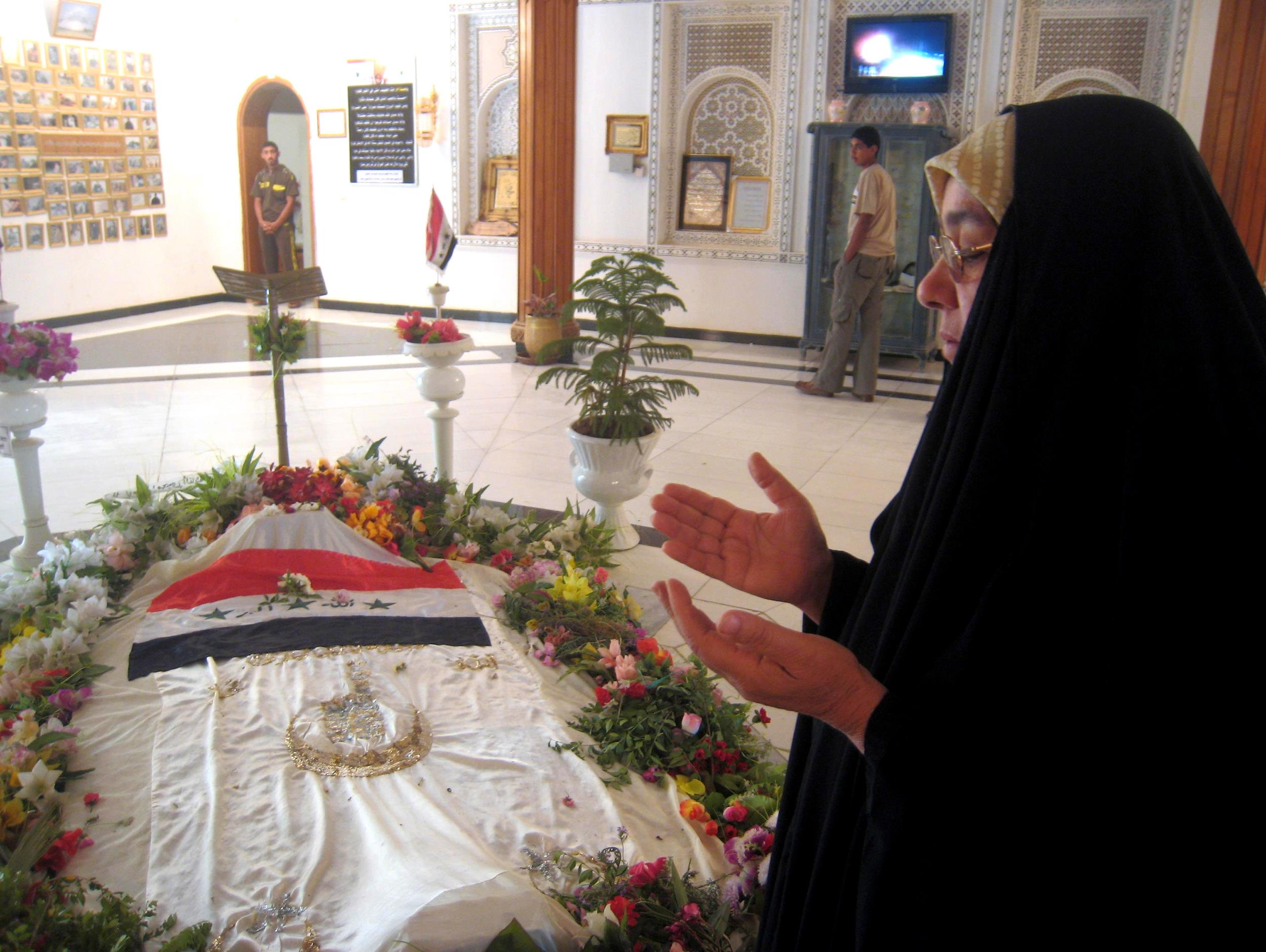 Image: A woman prays beside the tomb of former Iraqi dictator Saddam Hussein
