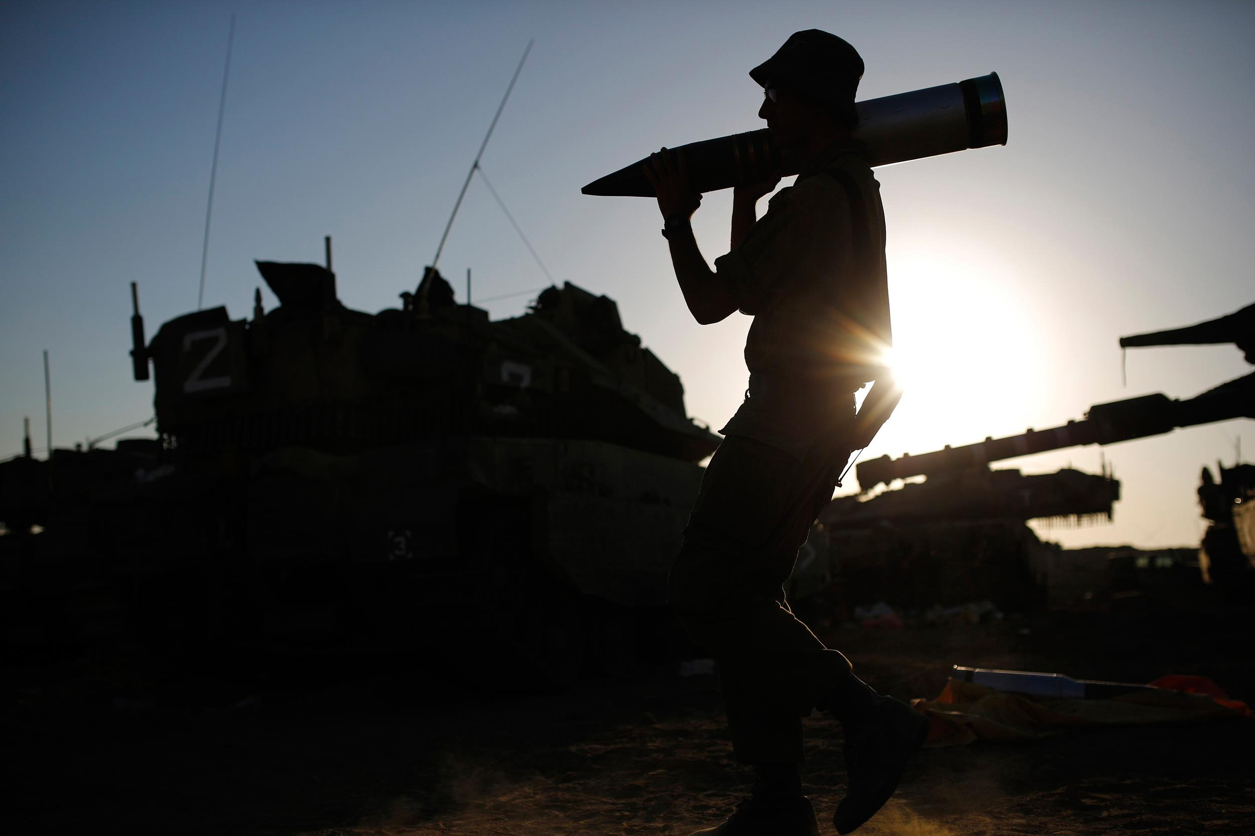 Image: An Israeli soldier carries a tank shell in a staging area near the border with the Gaza Strip