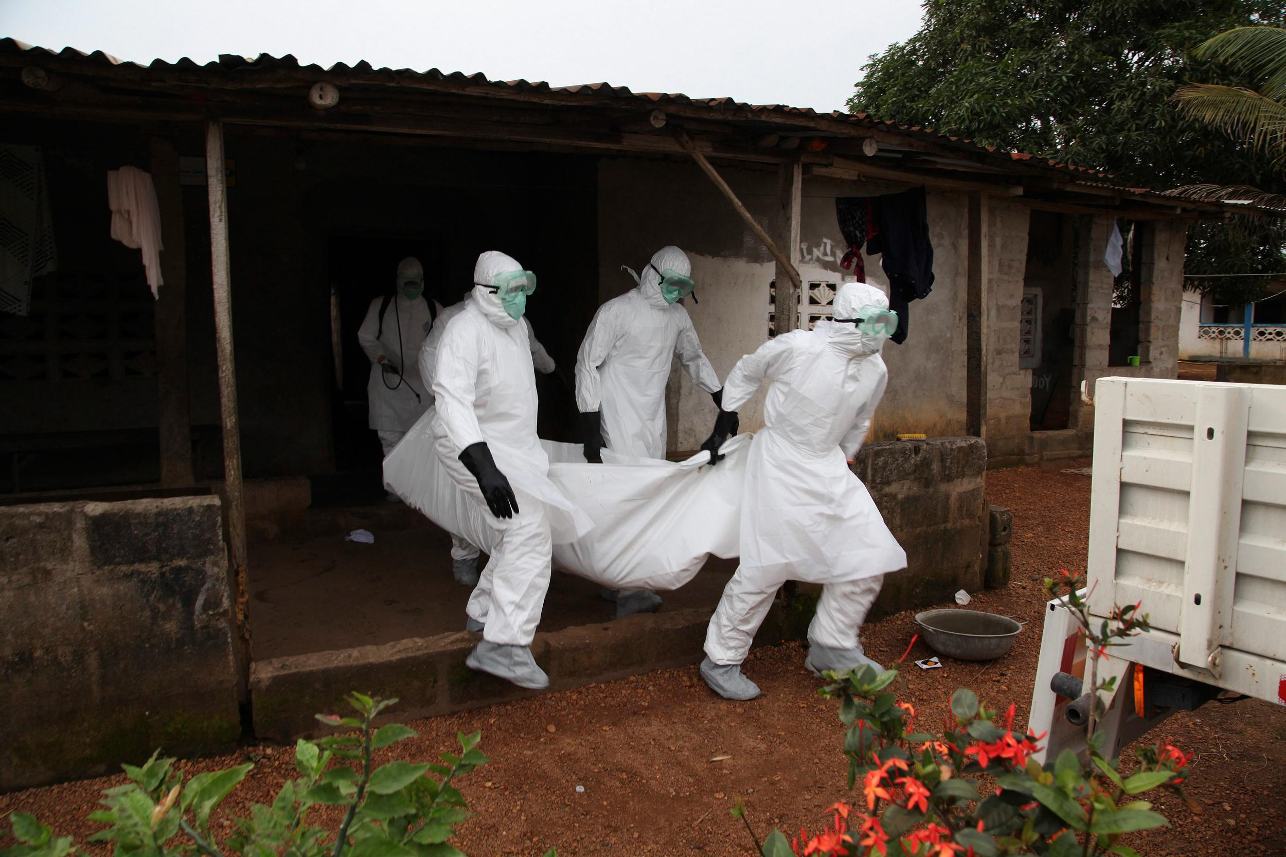 Image: Liberian nurses carry the body of an ebola victim