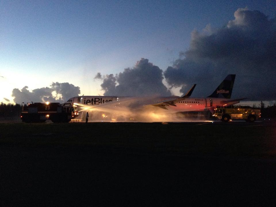 Image: A fire truck douses a JetBlue aircraft after its left engine caught fire